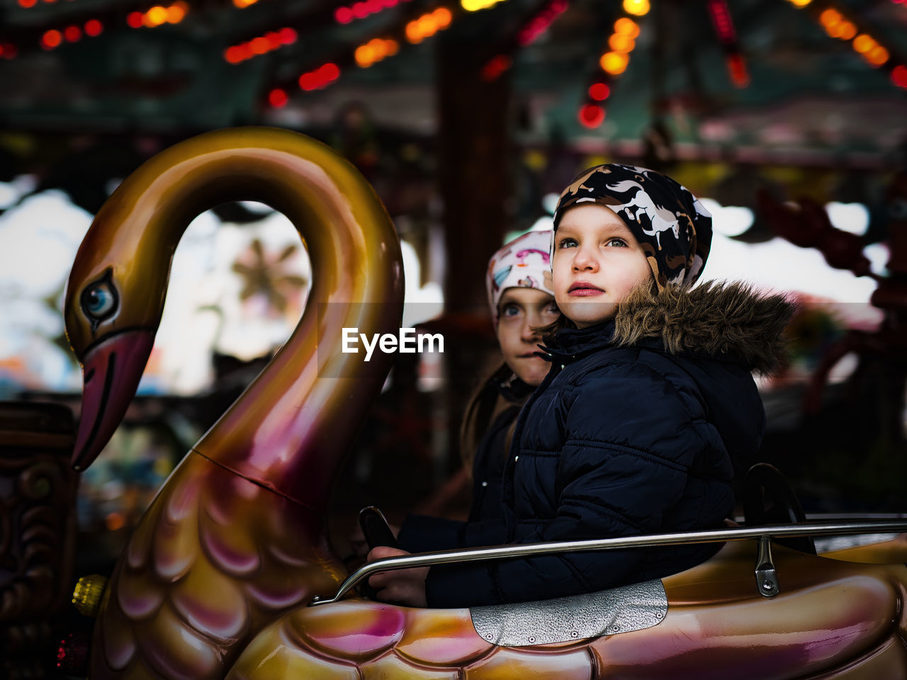 Girls Looking Away While Sitting On Amusement Park Ride