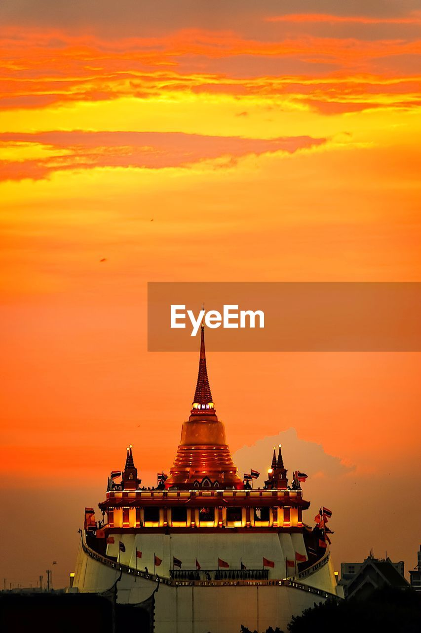 VIEW OF TEMPLE AGAINST BUILDING DURING SUNSET
