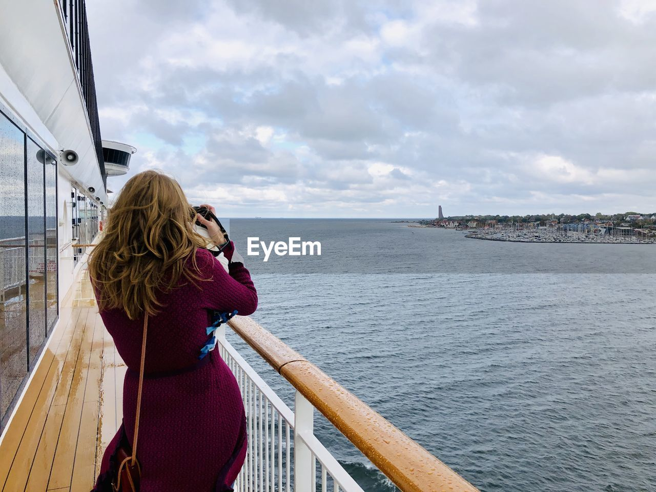 water, sky, cloud - sky, one person, real people, transportation, lifestyles, photographing, women, sea, mode of transportation, photography themes, adult, leisure activity, architecture, rear view, railing, connection, hair, wireless technology, hairstyle, outdoors