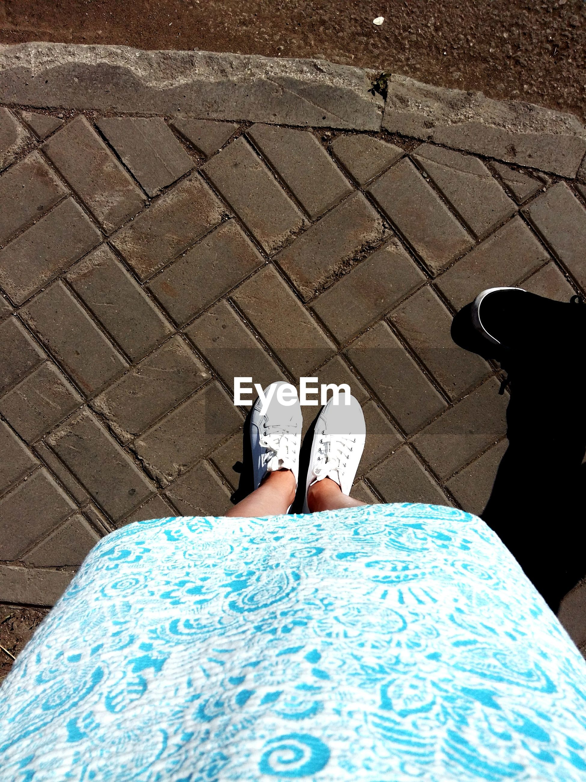 low section, person, lifestyles, personal perspective, high angle view, shoe, standing, street, leisure activity, human foot, men, shadow, unrecognizable person, cobblestone, paving stone, sunlight