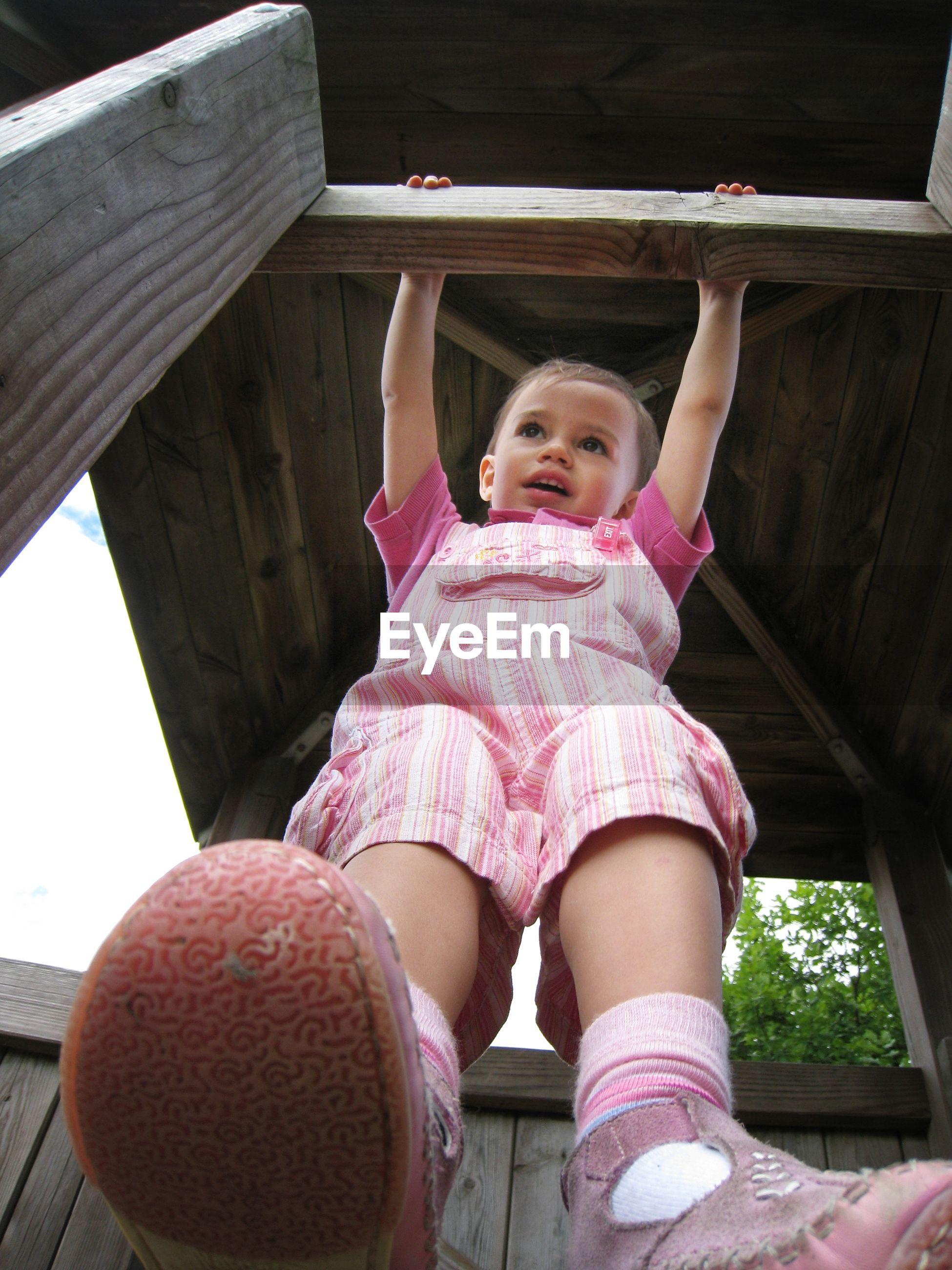 Low angle view of boy standing by railing