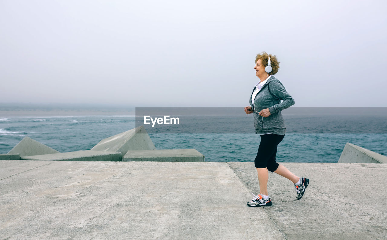 Senior woman standing on pier at beach against sky