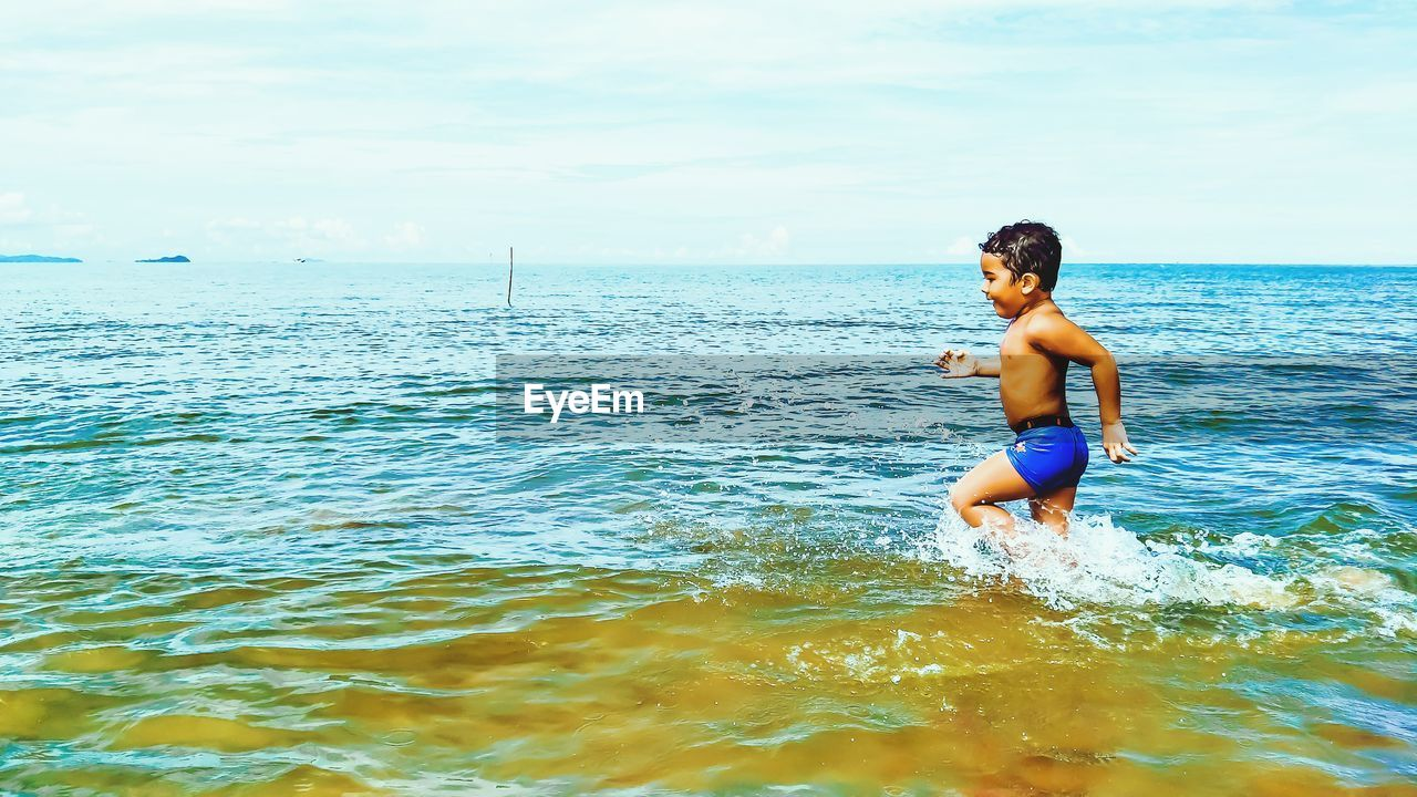 Side View Of Playful Shirtless Boy In Sea Against Sky