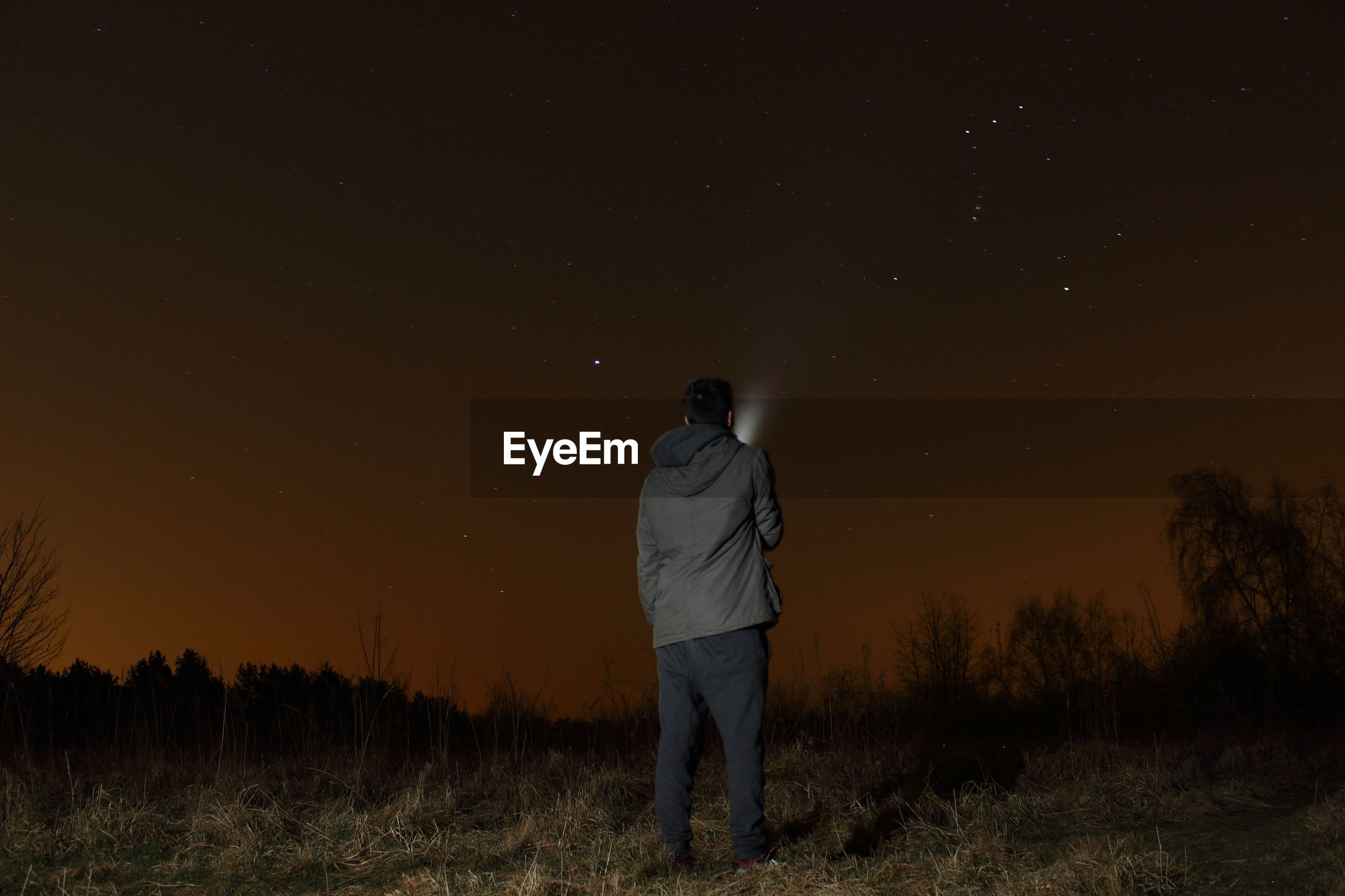 Rear view of man with flashlight standing on field against sky at night