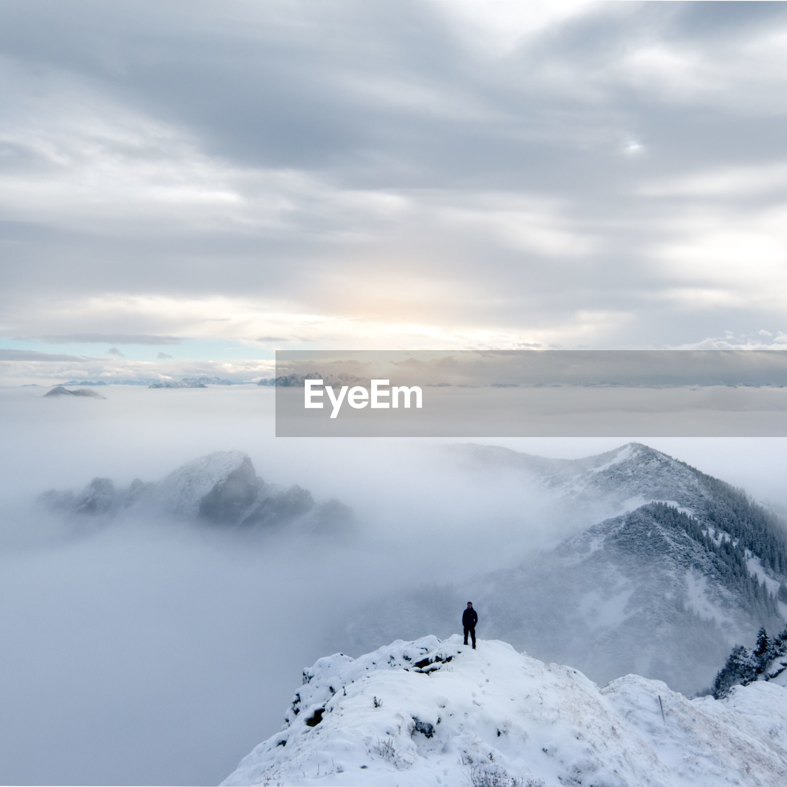 Person standing on snowcapped mountain against cloudy sky