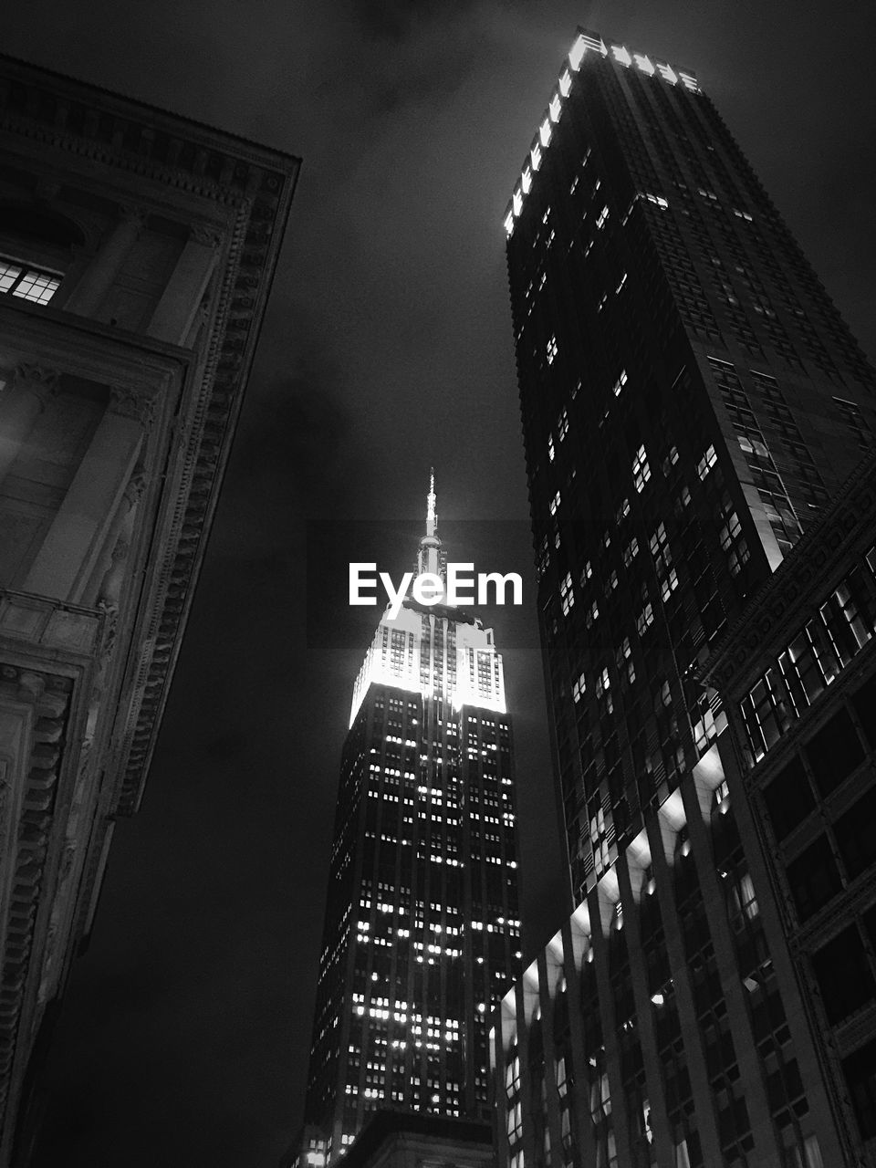 Exterior of illuminated langham place and empire state building against sky at night