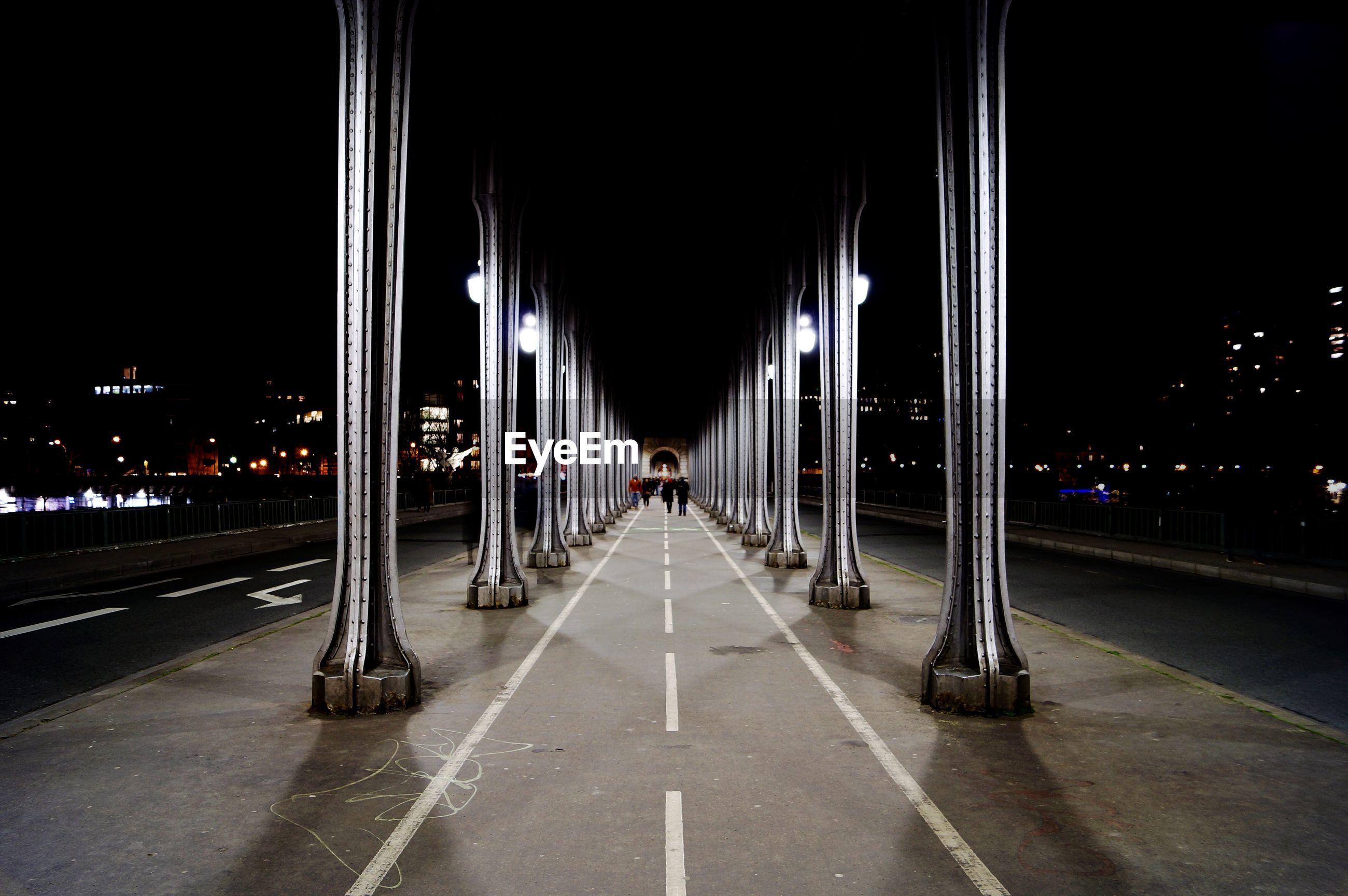 View of illuminated road under bridge in city at night