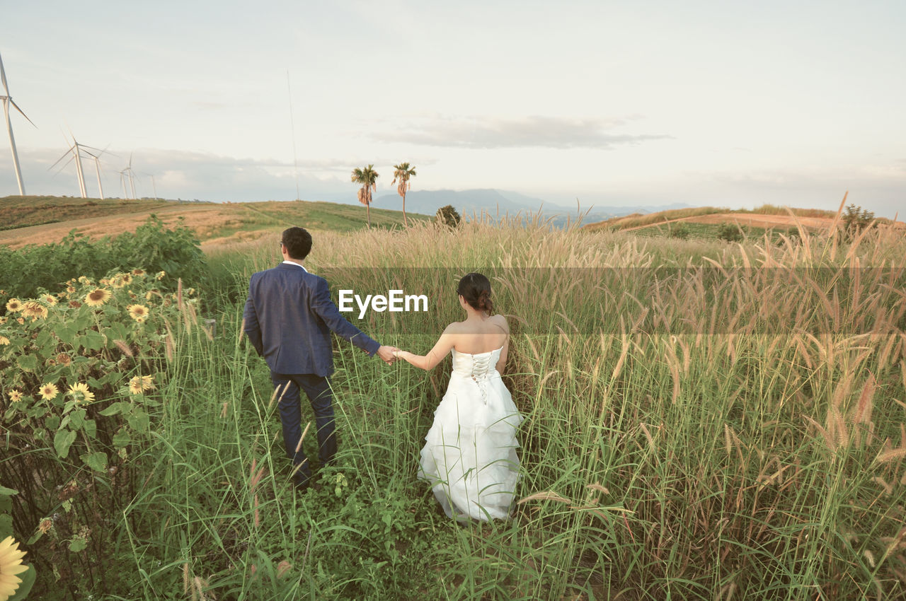 Young Couple Walking On Grassy Field Against Sky