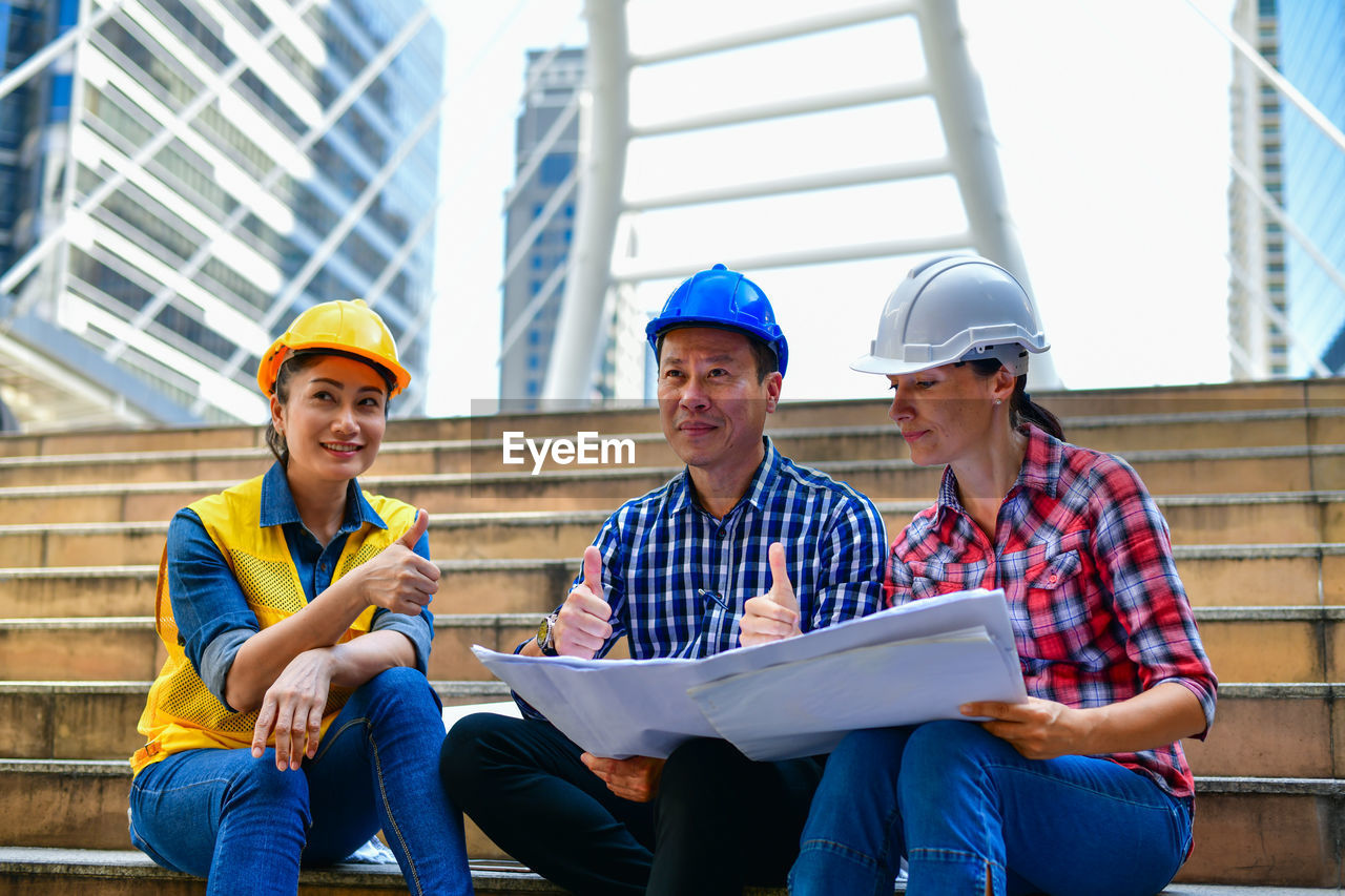 helmet, men, hardhat, males, young adult, hat, headwear, adult, occupation, real people, young men, sitting, construction industry, industry, architecture, working, holding, togetherness, design professional, teamwork, architect, blueprint