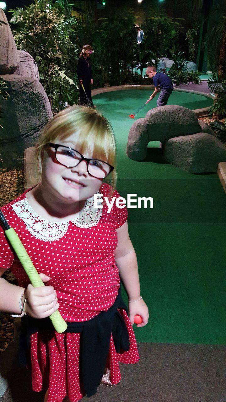 Portrait of happy girl holding golf club