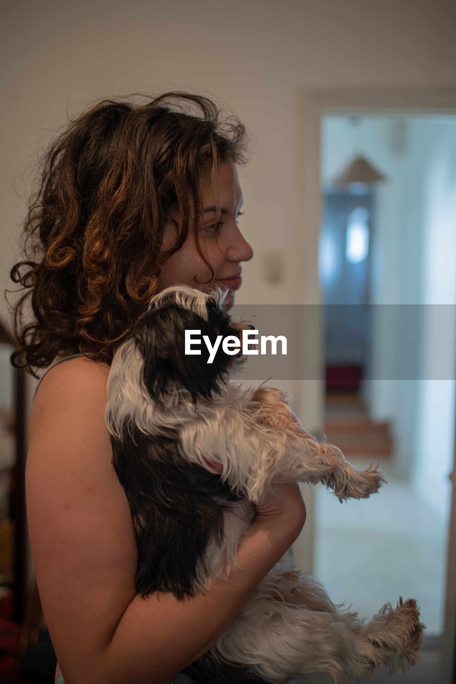 Side view of woman with dog at home