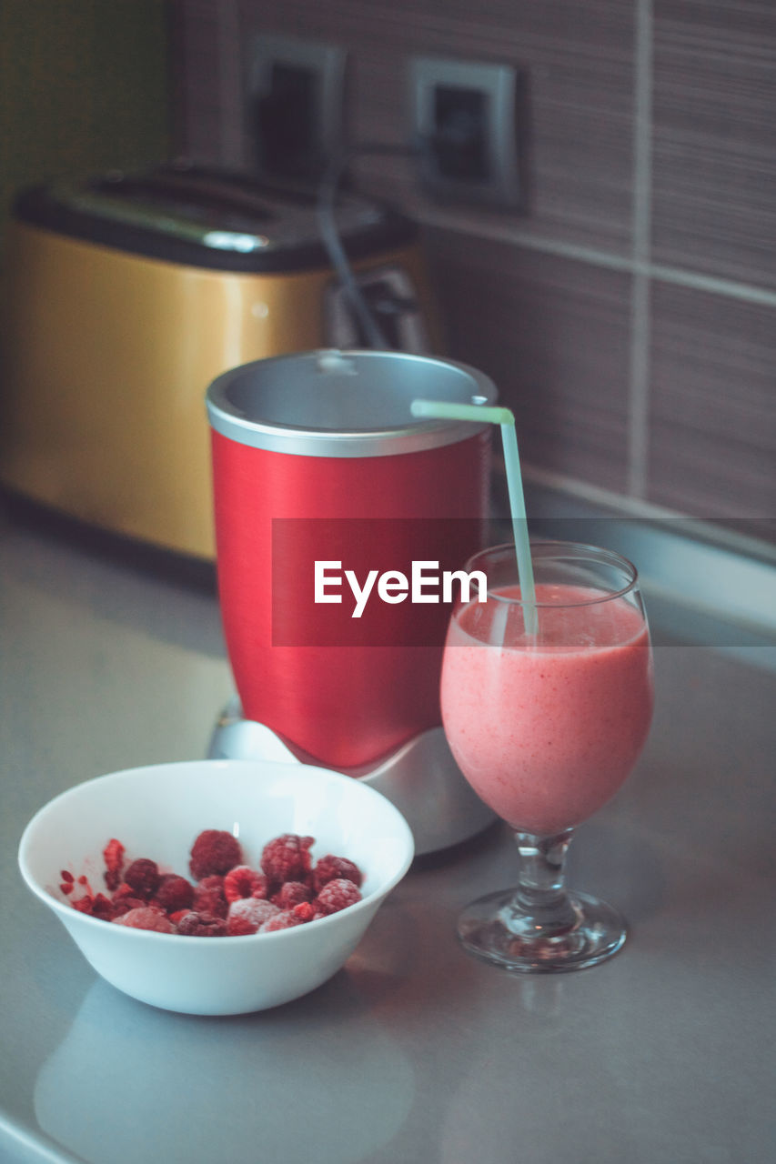 High angle view of drink with raspberries on table