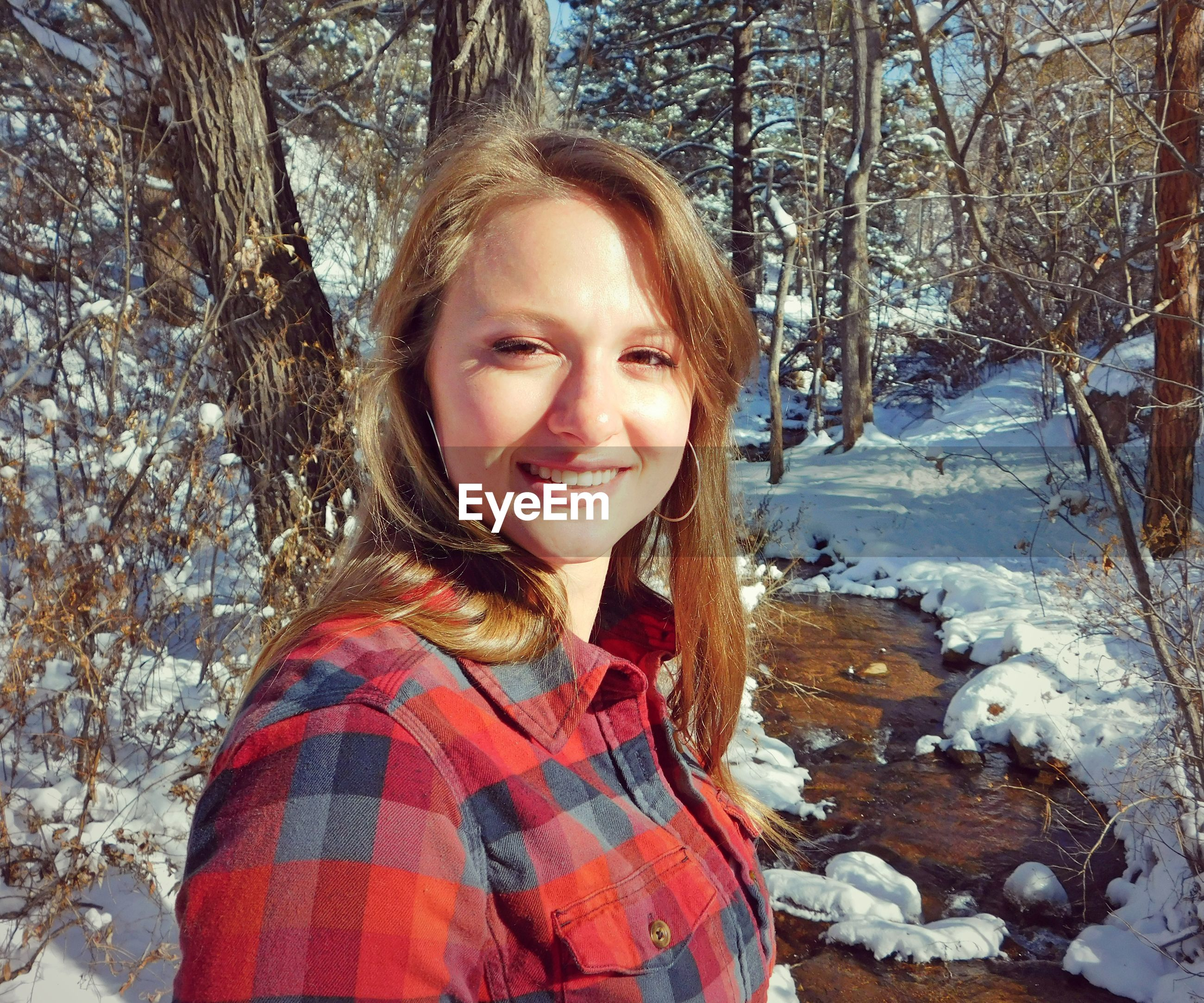 Portrait of smiling young woman in forest during winter