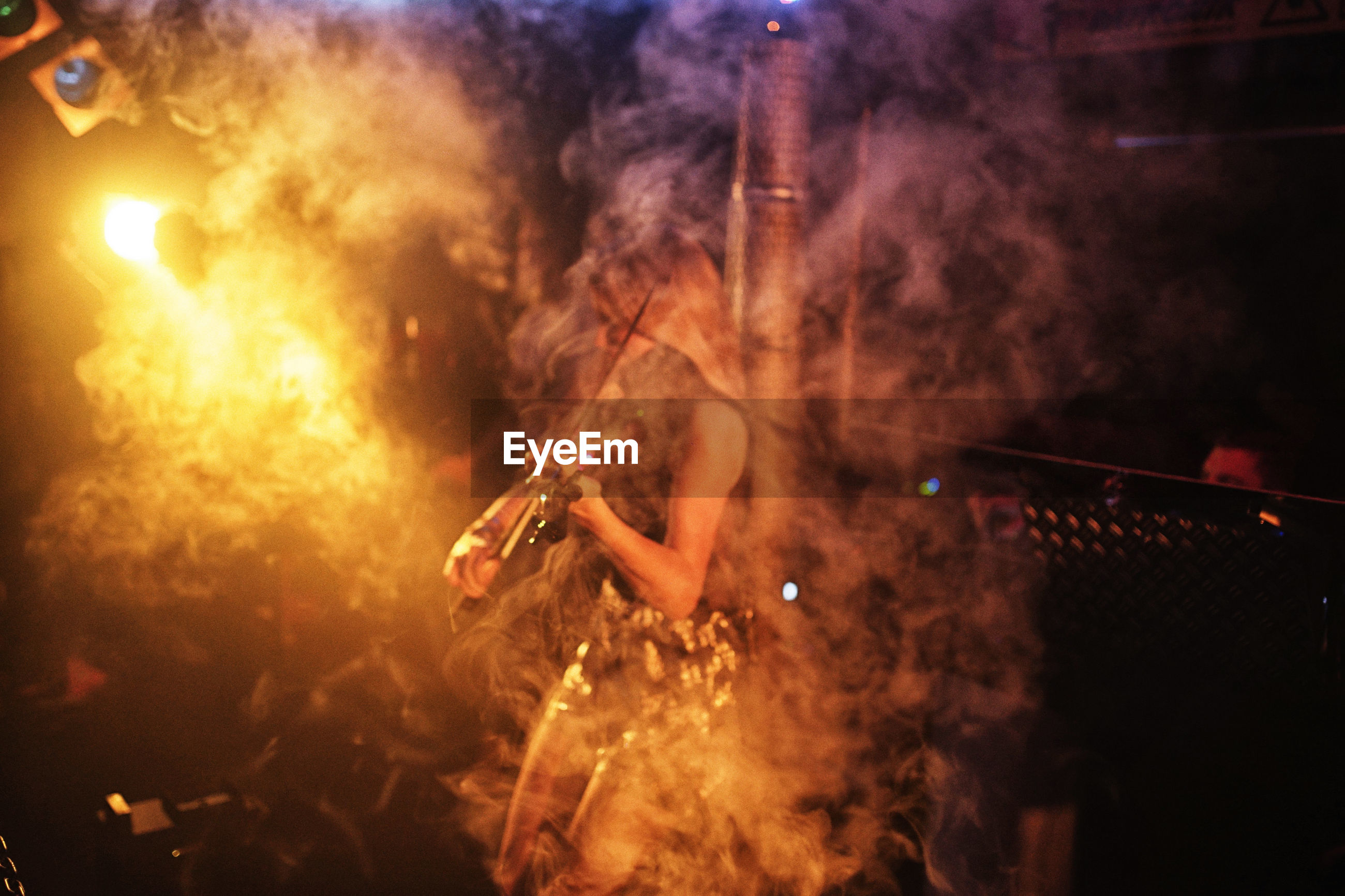 LOW ANGLE VIEW OF MAN HOLDING ILLUMINATED LIGHTING EQUIPMENT