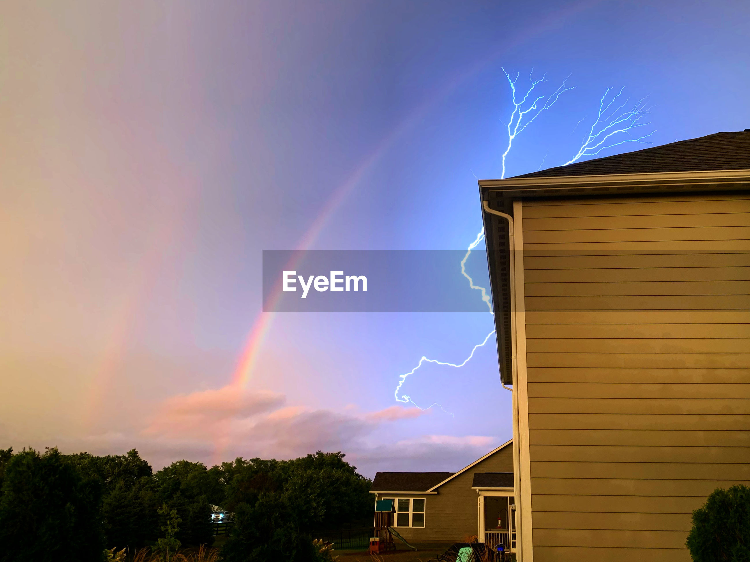 Low angle view of rainbow over building against sky