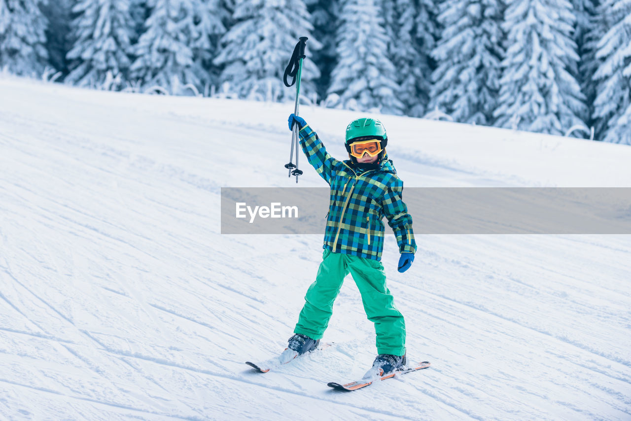 Full length portrait of boy holding ski poles on snow covered land