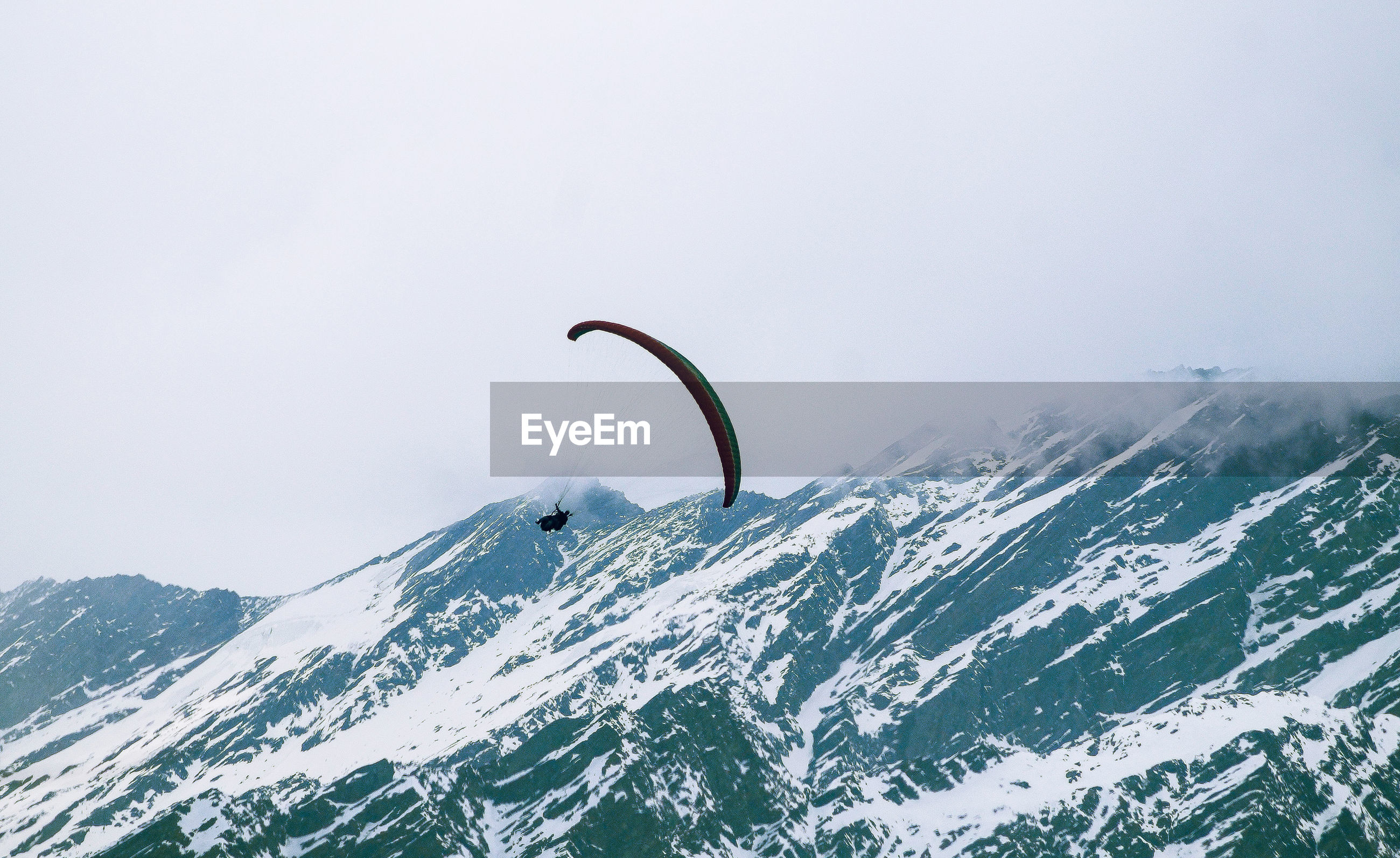Person paragliding over of snowcapped mountains against sky