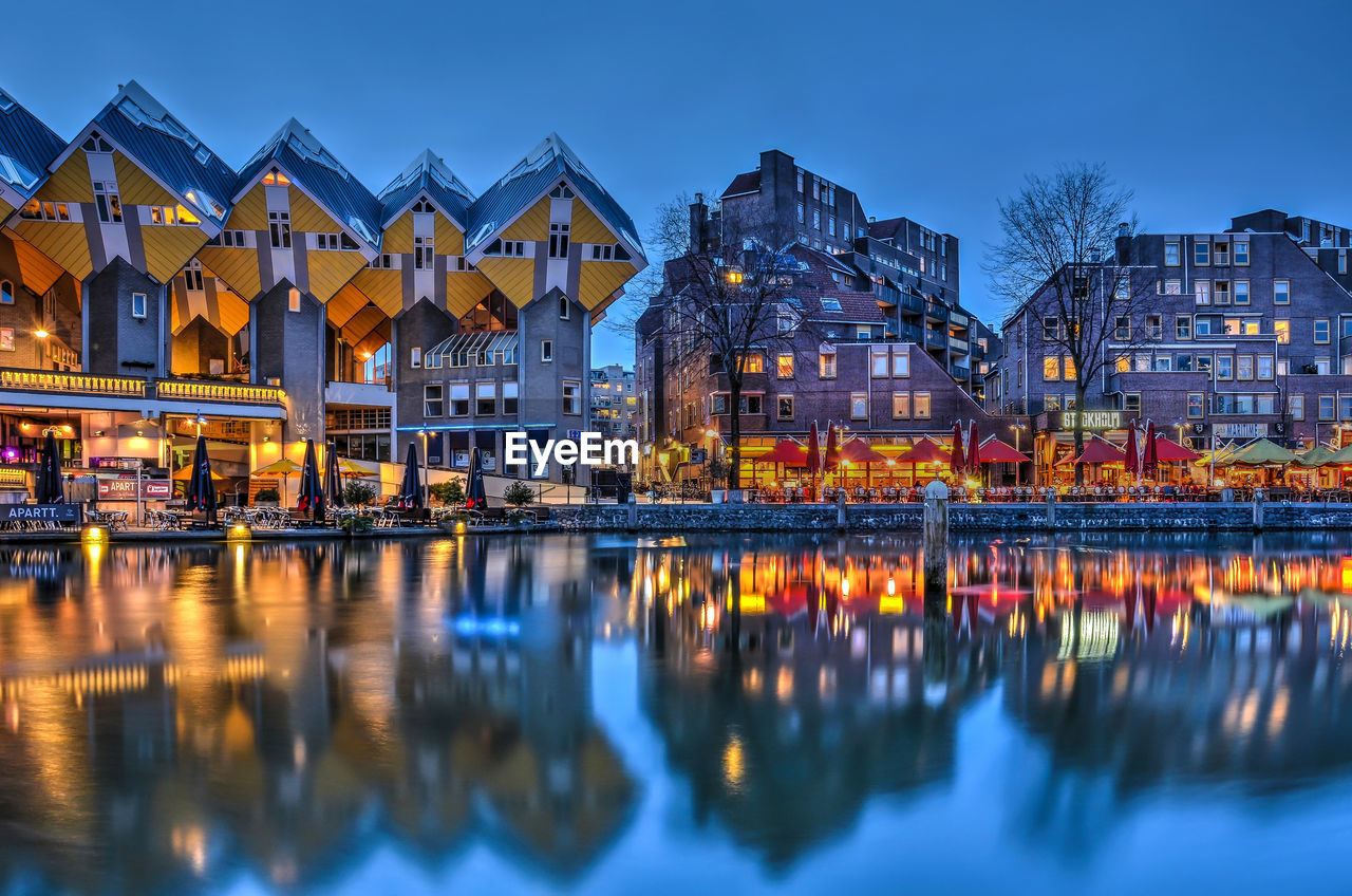 Illuminated Buildings By Lake Against Sky At Night