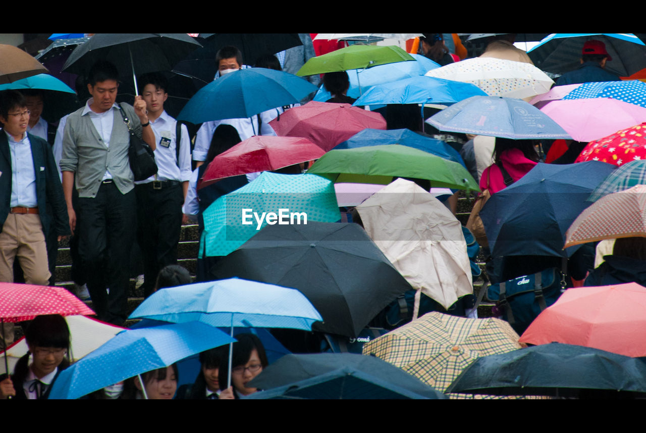 umbrella, sheltering, protection, rain, shelter, wet, weather, under, below, large group of people, women, enjoyment, outdoors, lifestyles, tent, men, real people, leisure activity, holding, city life, day, crowd, city, people, adult, adults only