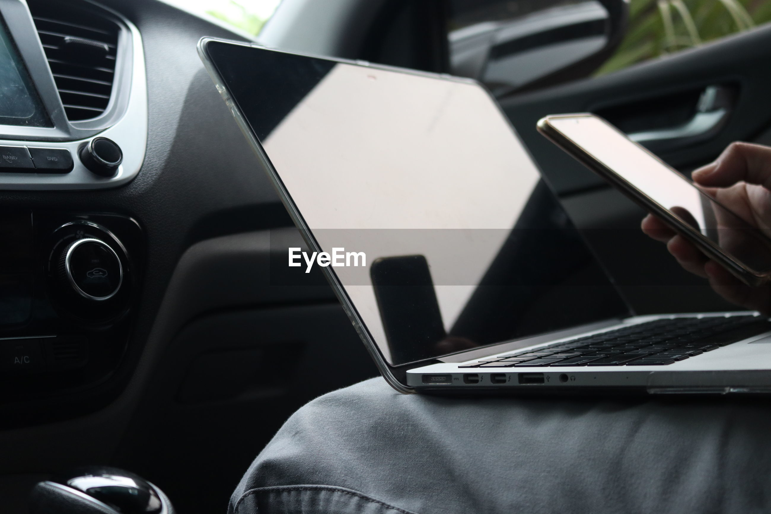 Cropped image of man using technologies while traveling in car