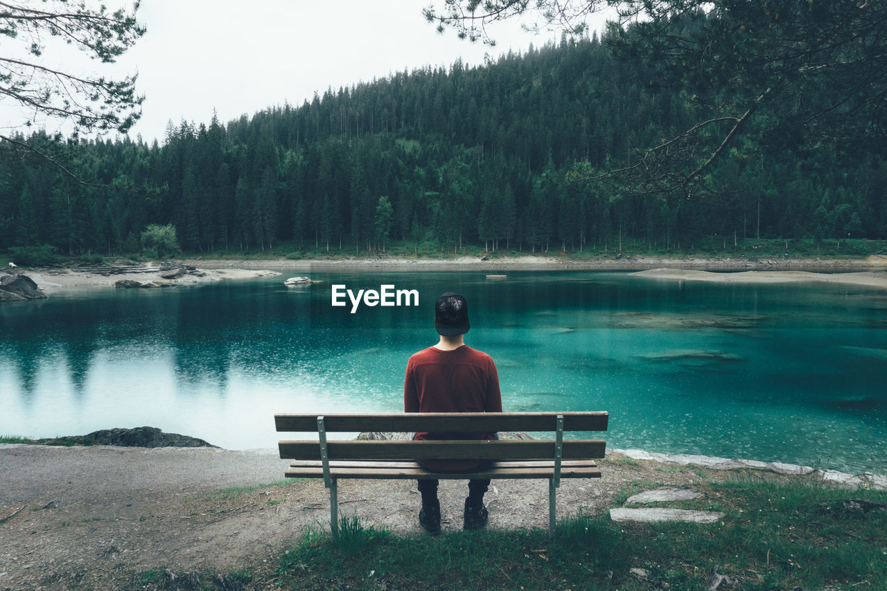 Rear View Of Man Sitting On Bench While Looking At Caumasee Lake Against Trees
