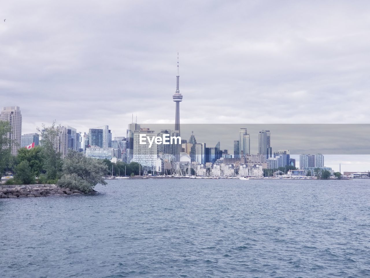 Buildings in city at waterfront against cloudy sky