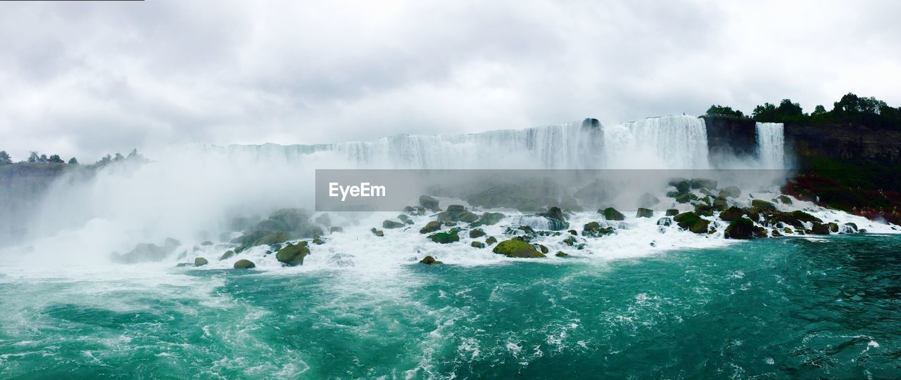 Panoramic view of waterfall against cloudy sky