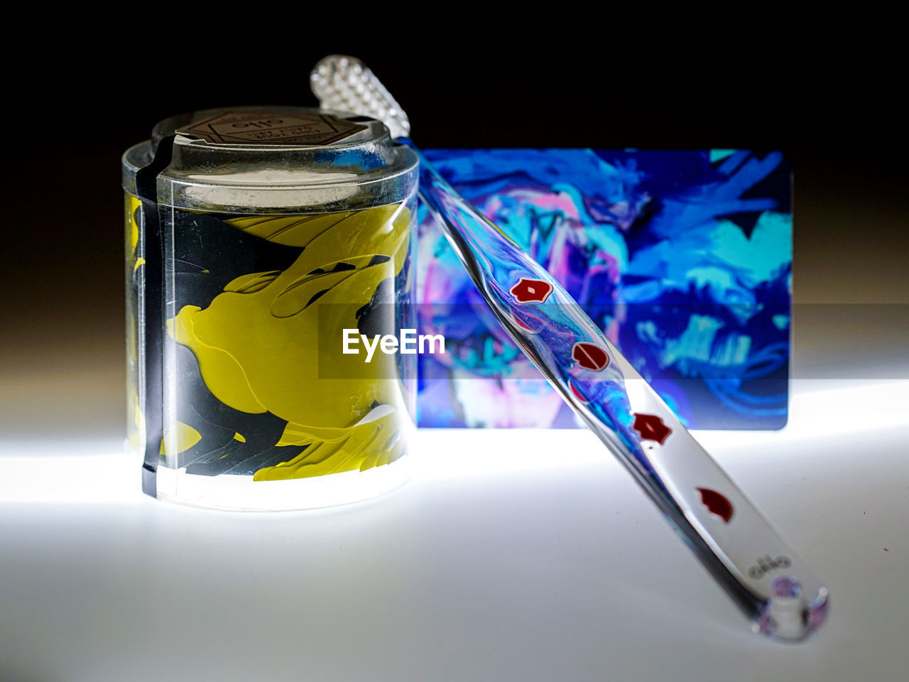 indoors, close-up, no people, blue, still life, container, studio shot, transparent, communication, glass - material, focus on foreground, jar, table, yellow, art and craft, multi colored, paint, high angle view, brush, paintbrush, black background