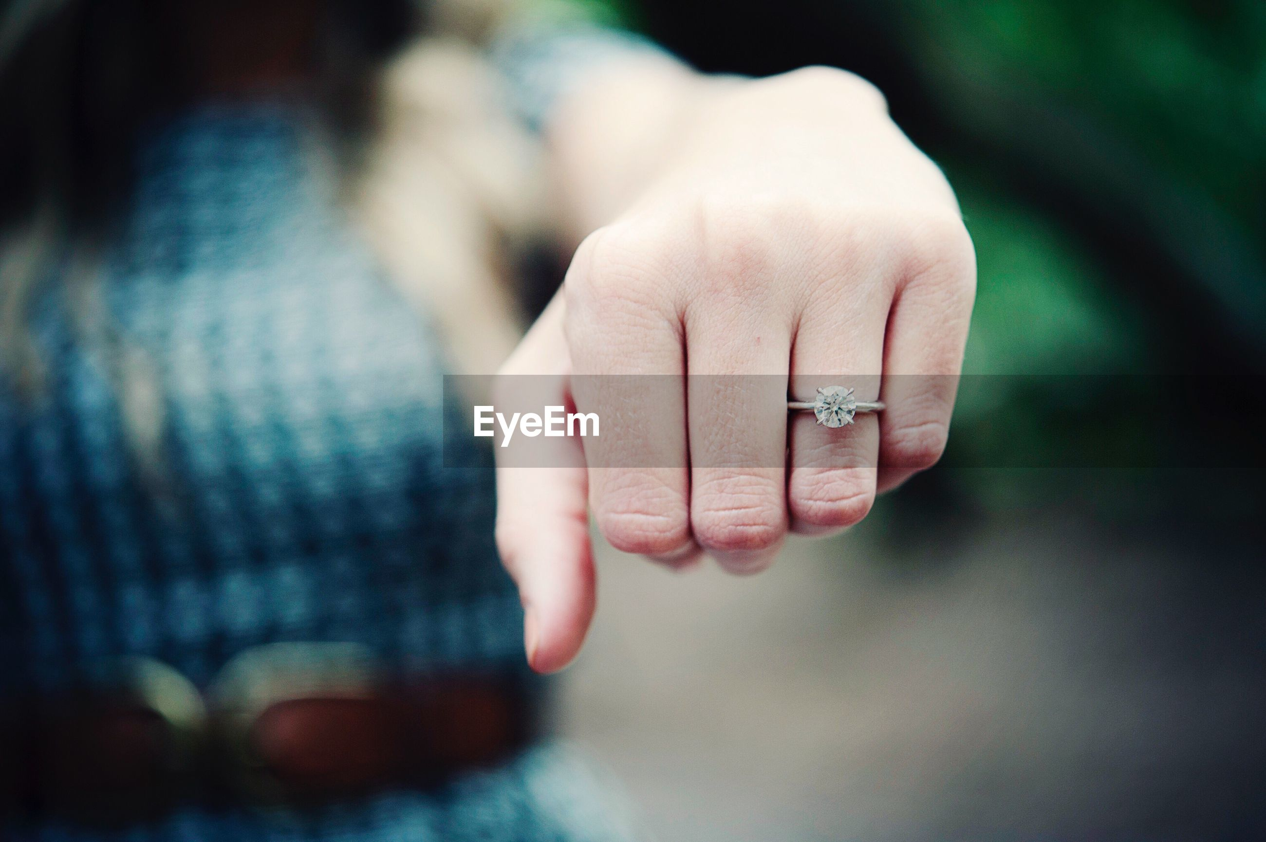 Close-up of diamond ring in human finger