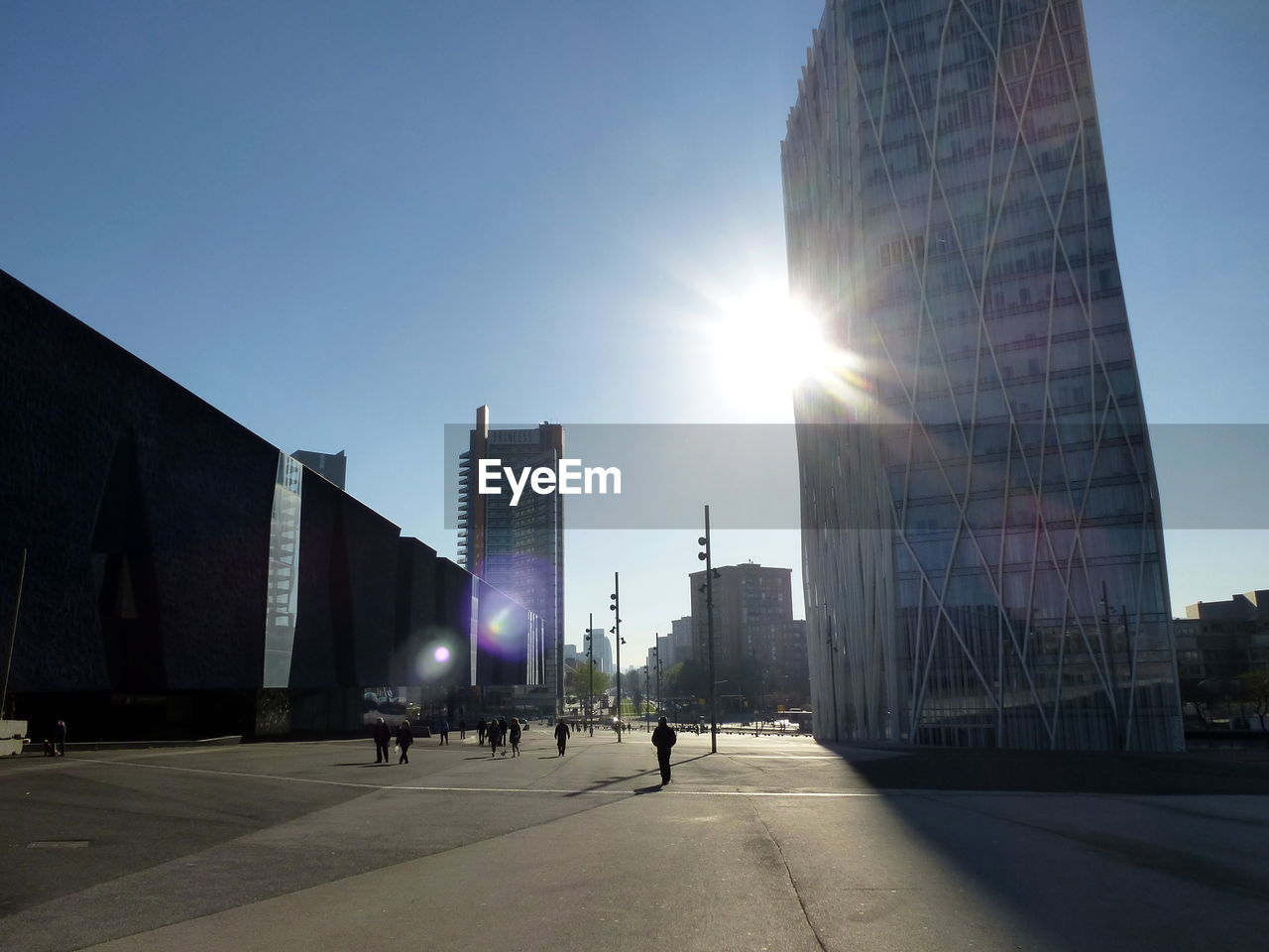 architecture, building exterior, sky, built structure, city, lens flare, office building exterior, sunlight, nature, sun, building, sunbeam, modern, office, skyscraper, clear sky, day, tall - high, real people, street, outdoors, bright, financial district