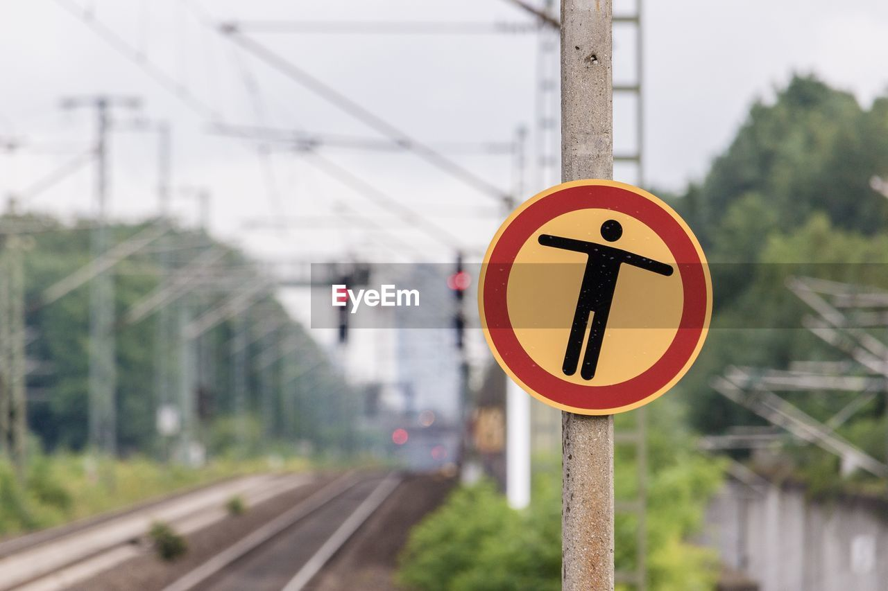 rail transportation, transportation, track, sign, focus on foreground, railroad track, public transportation, mode of transportation, communication, day, guidance, signal, railway signal, geometric shape, no people, shape, circle, road sign, train, connection, outdoors, electricity