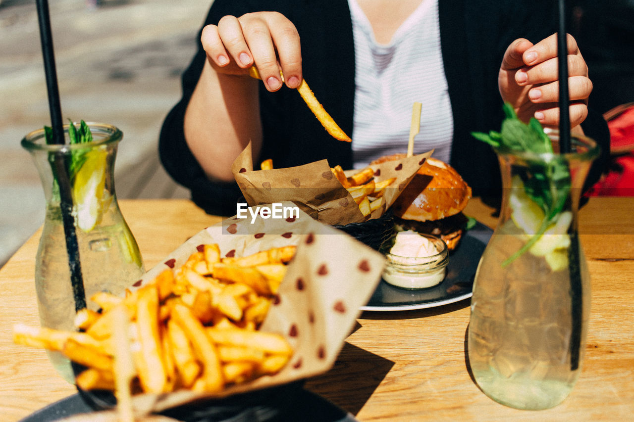 Midsection Of Woman Having French Fries While Sitting At Table
