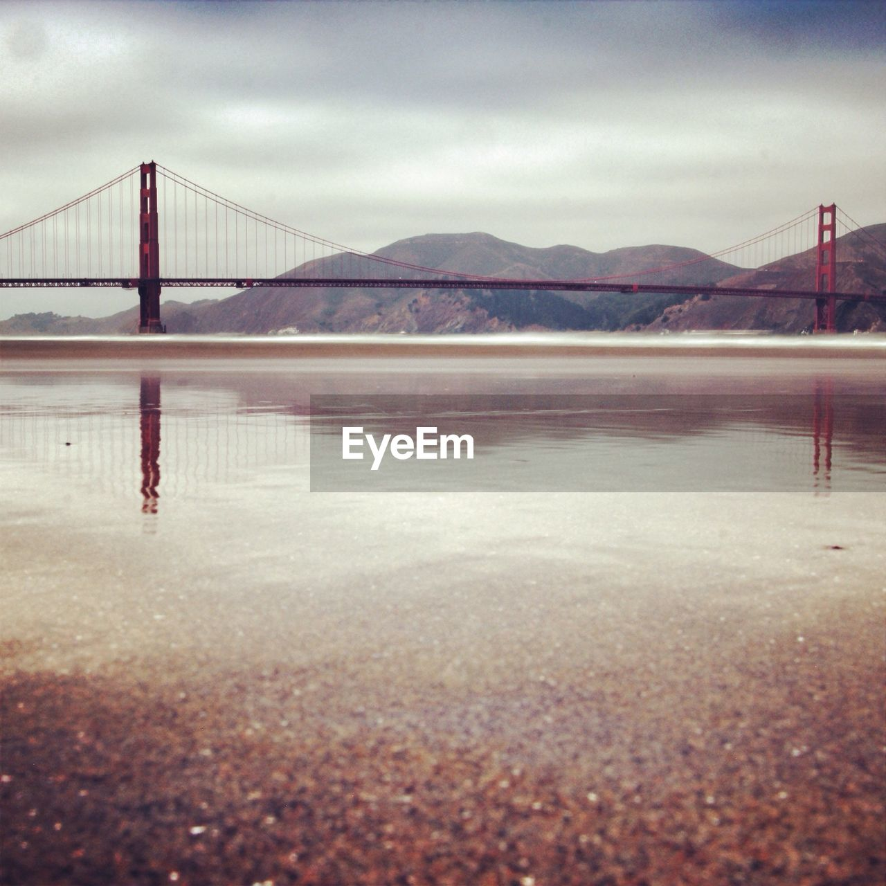 Golden gate bridge over sea by mountains against cloudy sky