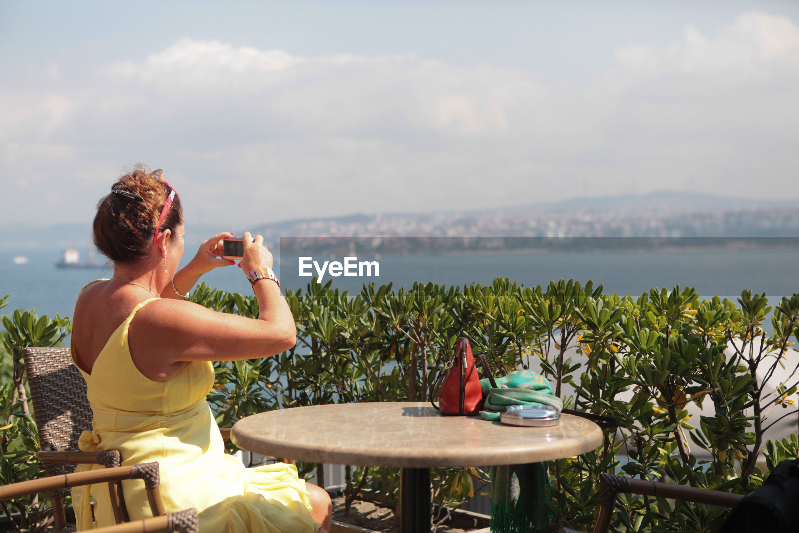 Woman photographing sea through mobile phone while sitting at table