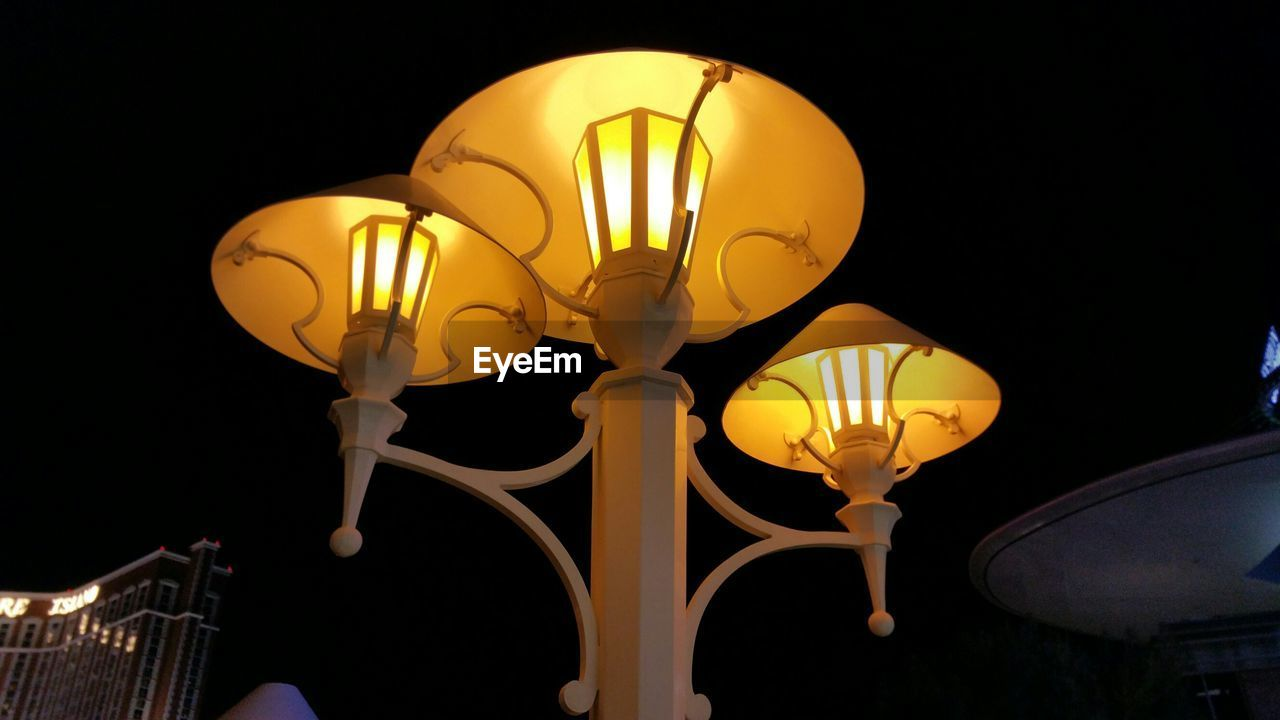 Low Angle View Of Illuminated Lamps At Night