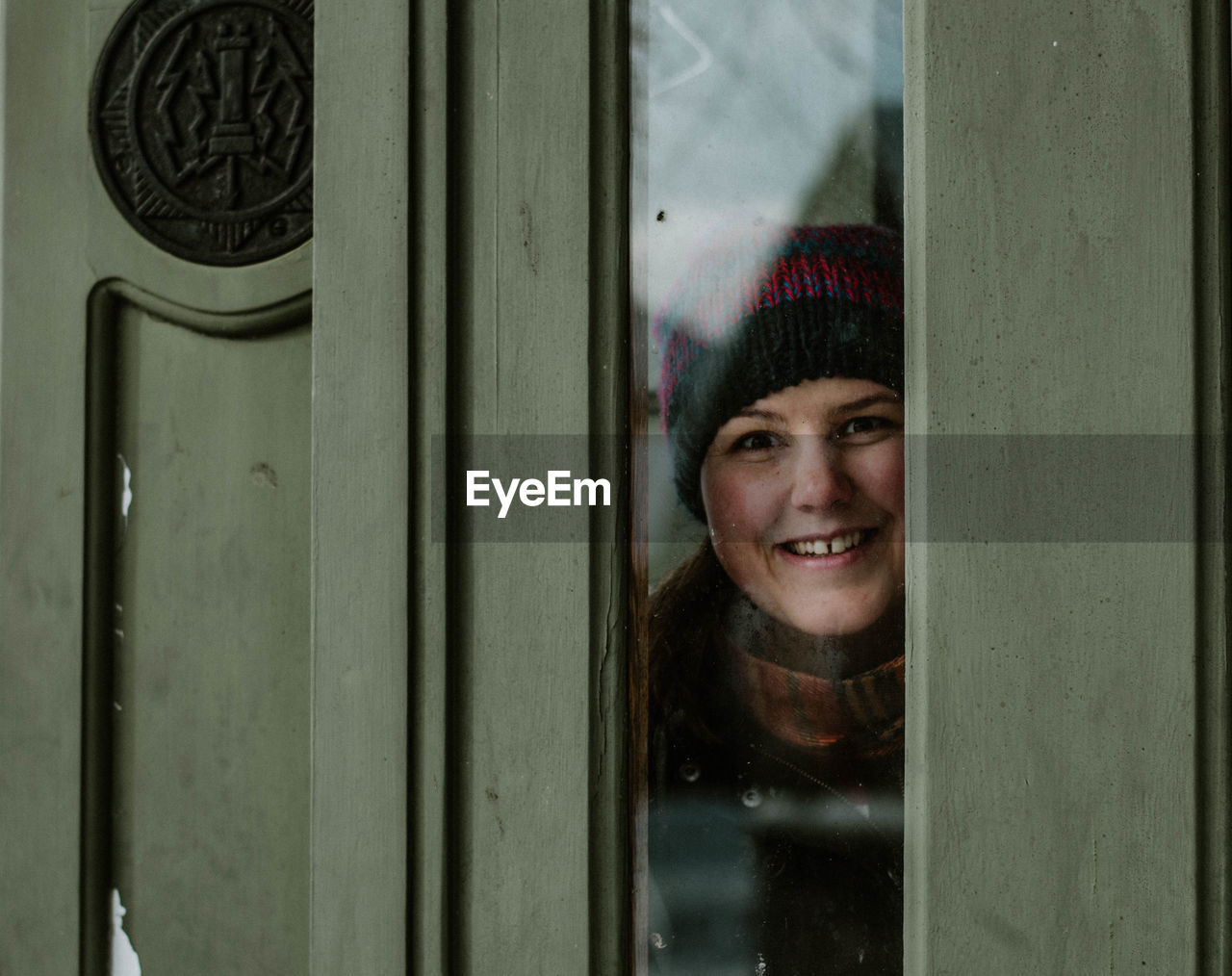 Portrait Of Smiling Young Woman Against Door