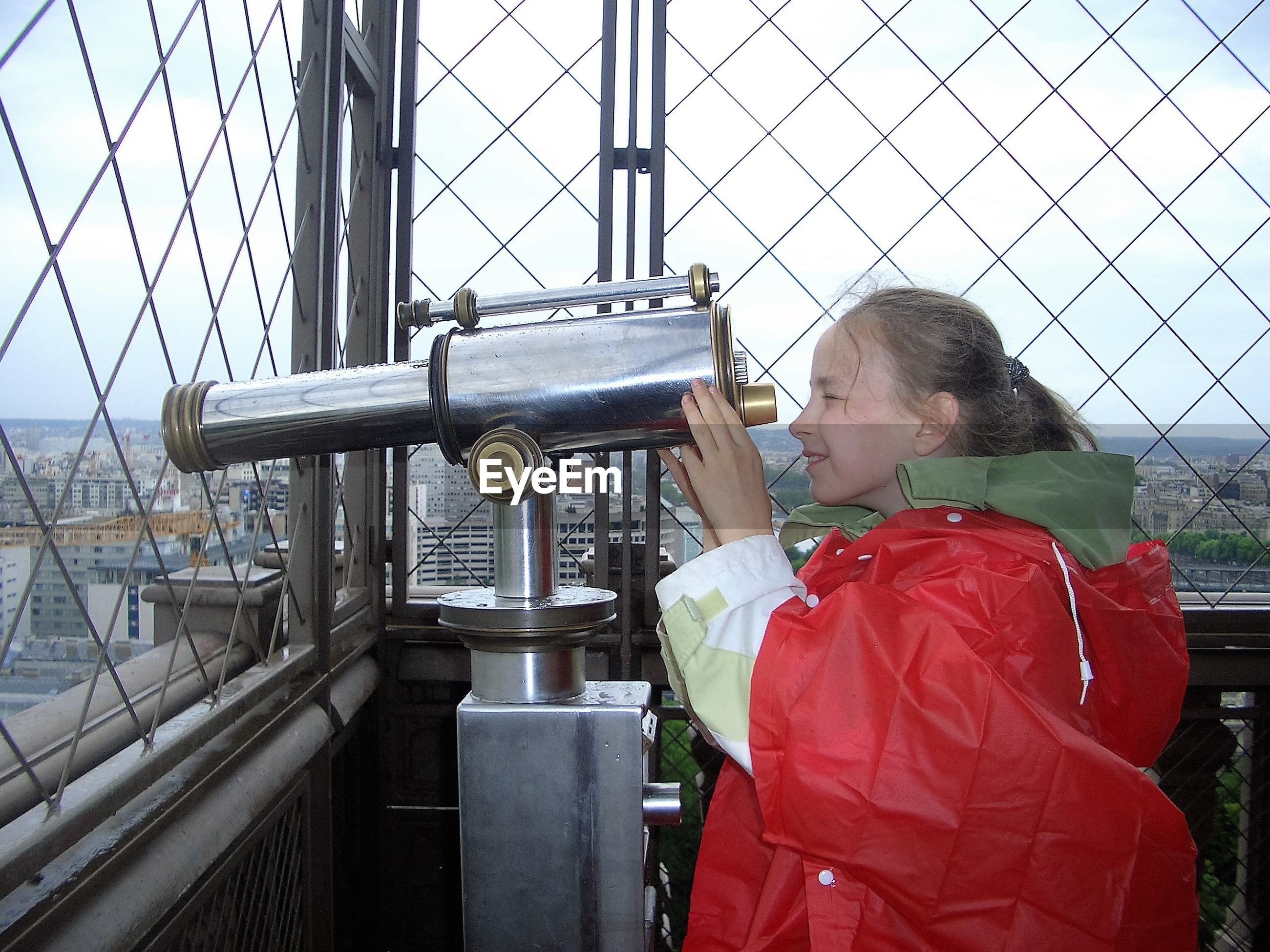 Side view of girl using hand-held telescope at eiffel tower