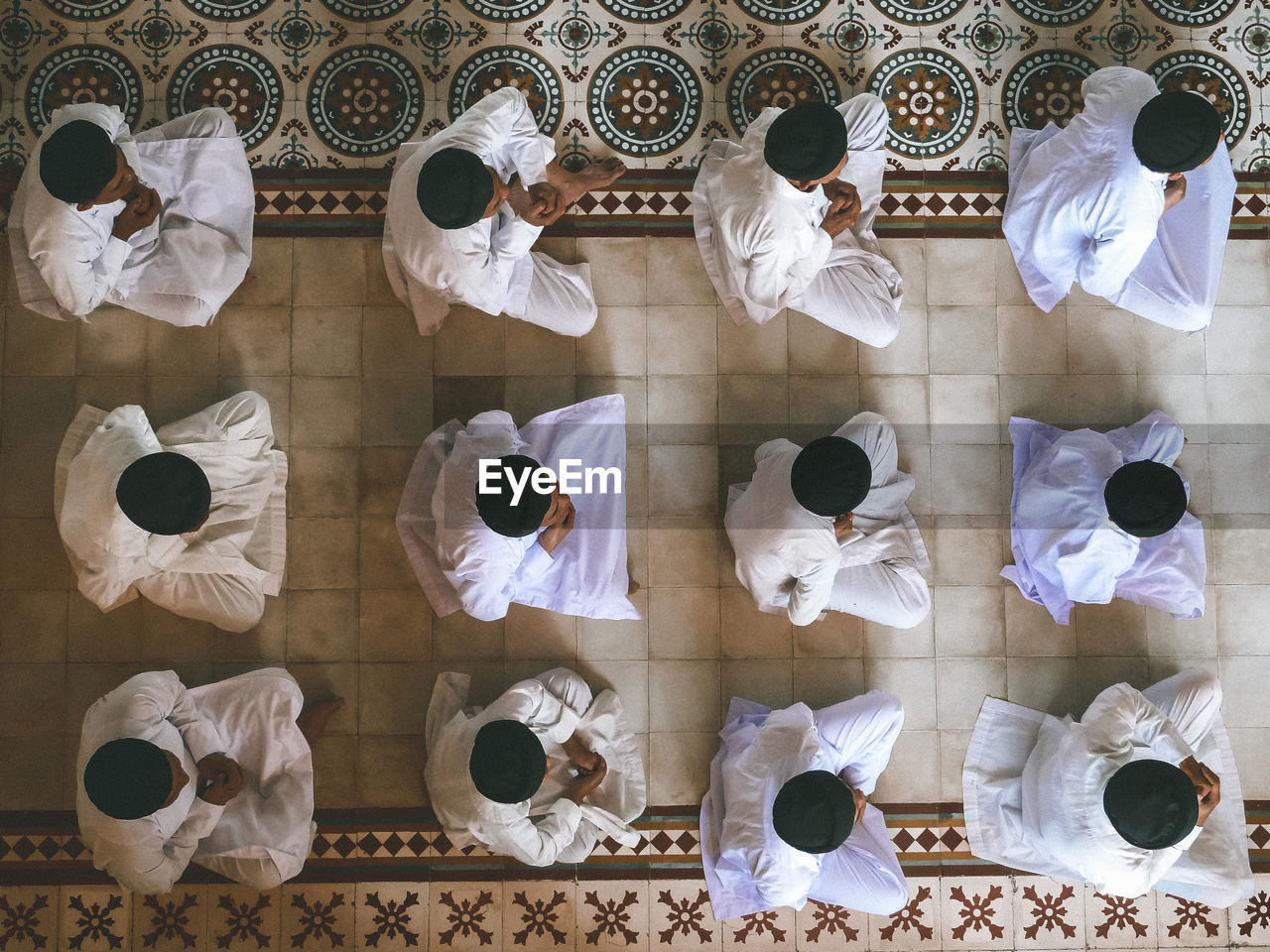 HIGH ANGLE VIEW OF PEOPLE STANDING ON WHITE TABLE