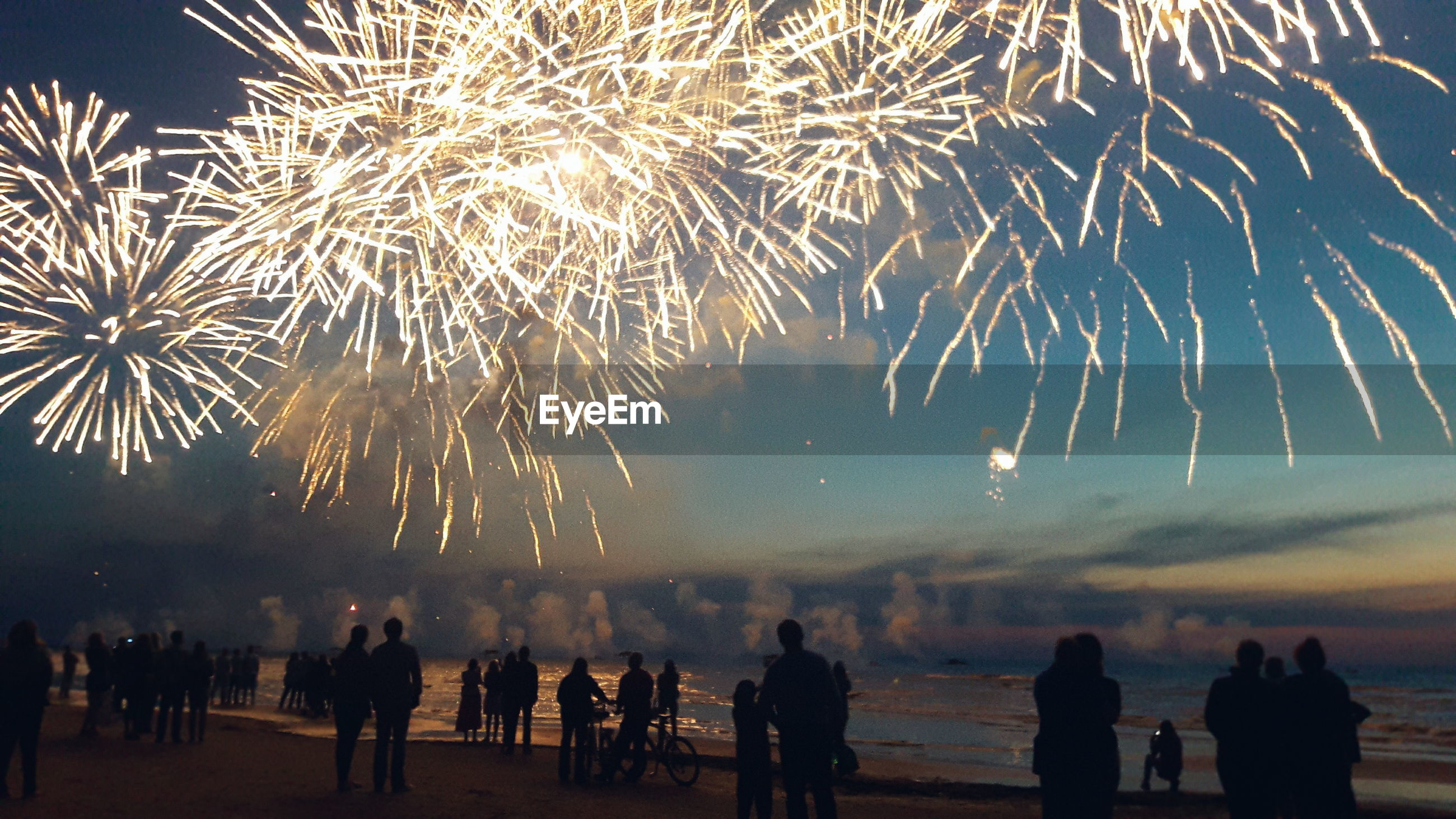 Silhouette people enjoying illuminated firework exploding against sky at beach during sunset