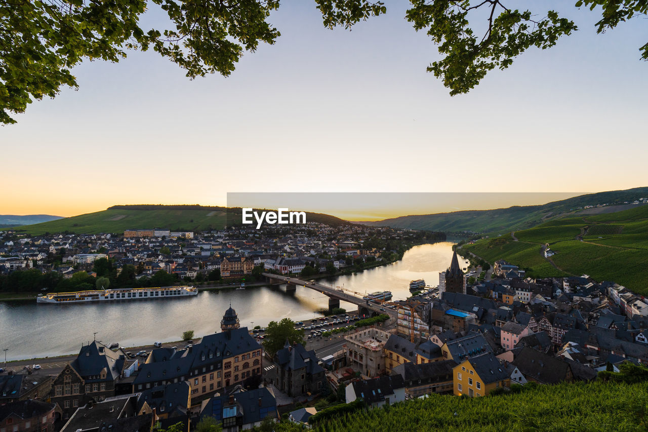 HIGH ANGLE VIEW OF TOWNSCAPE BY RIVER AGAINST CLEAR SKY
