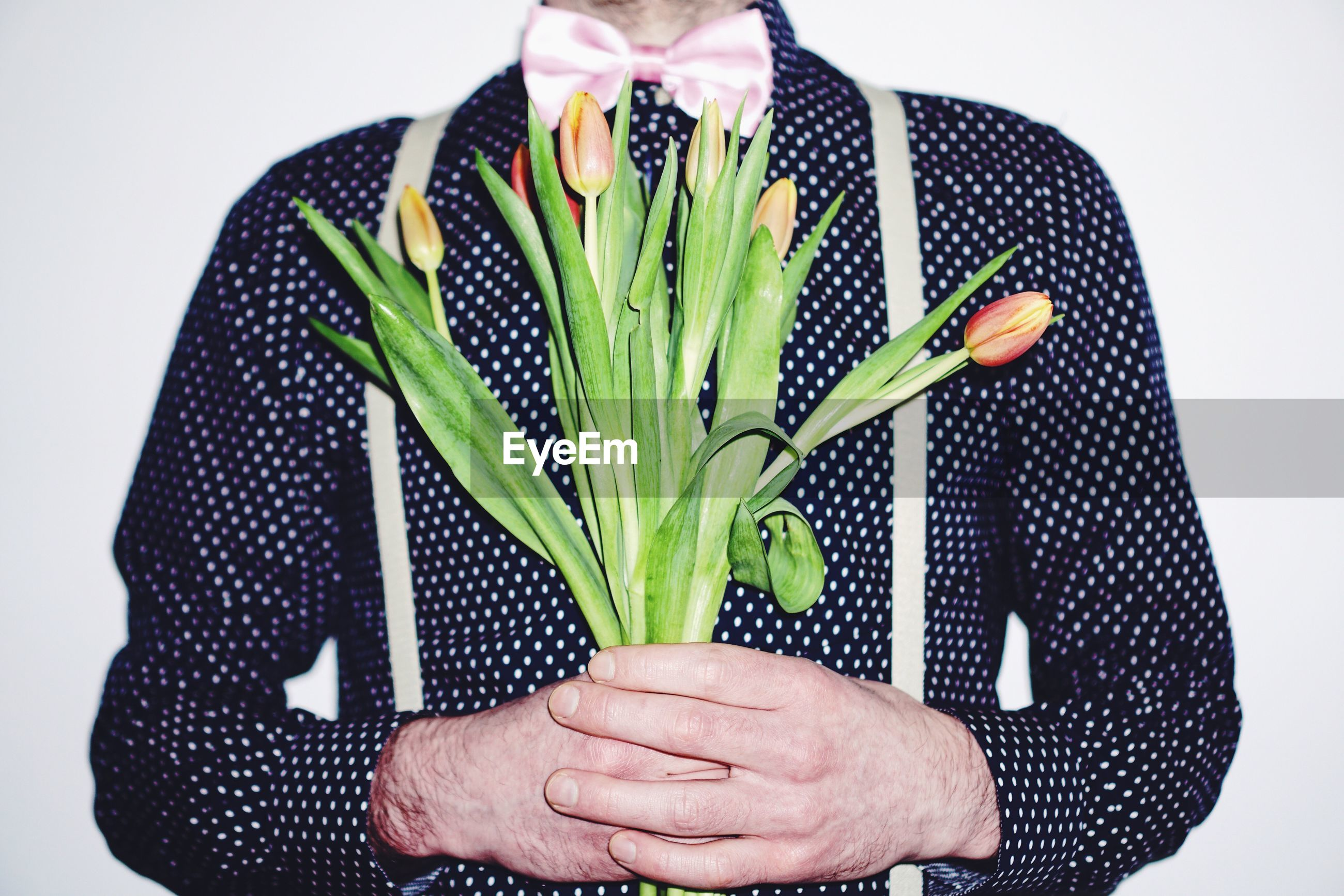 Close-up of man holding bunch of flowers over white background