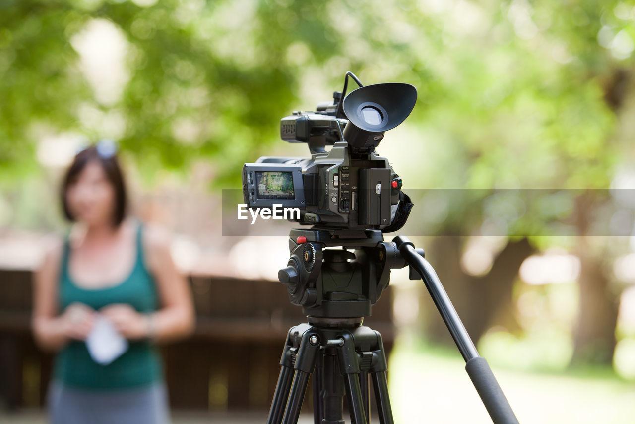 Close-up of television camera against woman at park