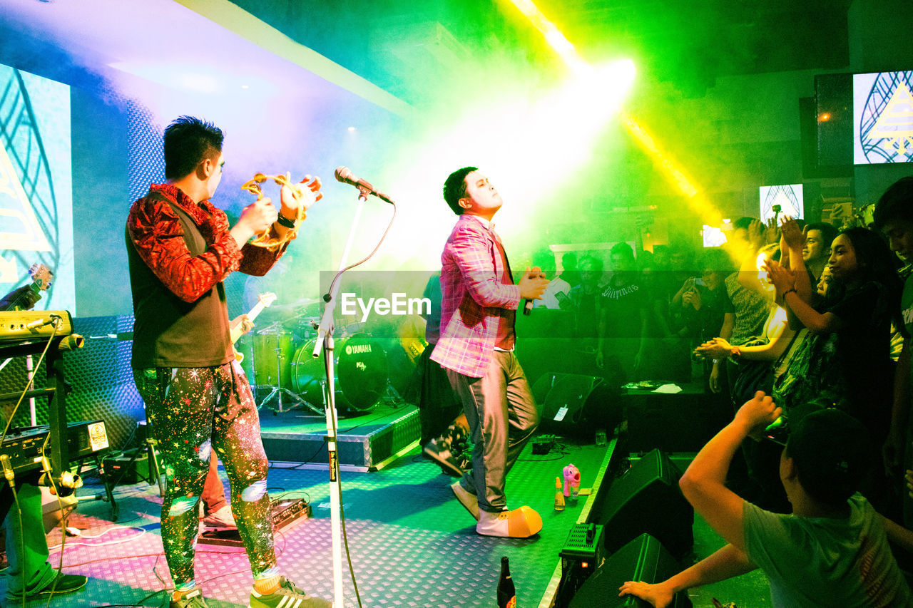 nightlife, real people, arts culture and entertainment, enjoyment, excitement, large group of people, performance, fun, indoors, leisure activity, lifestyles, nightclub, music, stage - performance space, men, youth culture, illuminated, night, togetherness, crowd, musician, young adult, adult, people