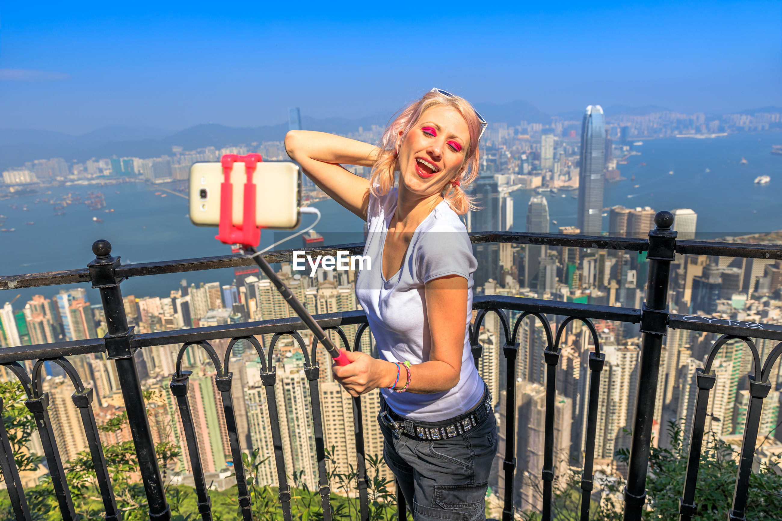 Woman taking selfie with mobile phone standing by railing against cityscape
