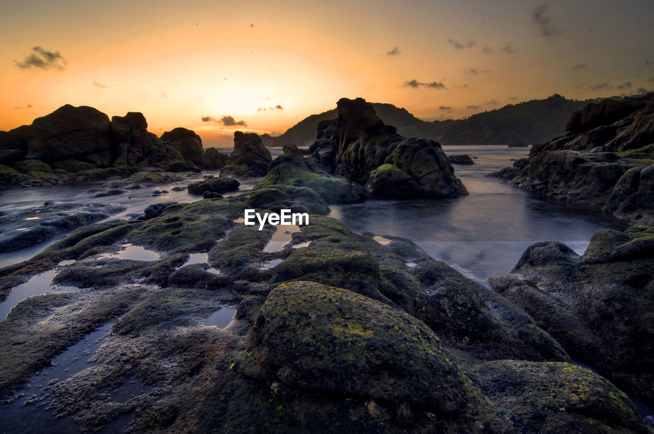 Wediombo Beach in Gunung Kidul is one of the beautiful southern beaches of Java to enjoy the sunset. Sunset Sky Beauty In Nature Water Scenics - Nature Rock Sea Solid Rock - Object Cloud - Sky Tranquil Scene Nature No People Land Orange Color Tranquility Idyllic Beach Outdoors Power In Nature Flowing Water