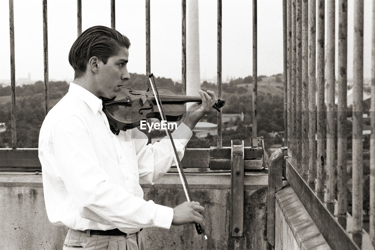 Side view of man playing violin while standing by railing