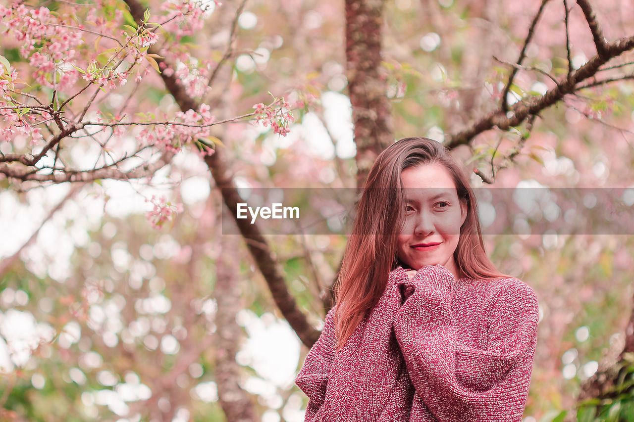 Mid adult woman wearing sweater while standing against cherry tree