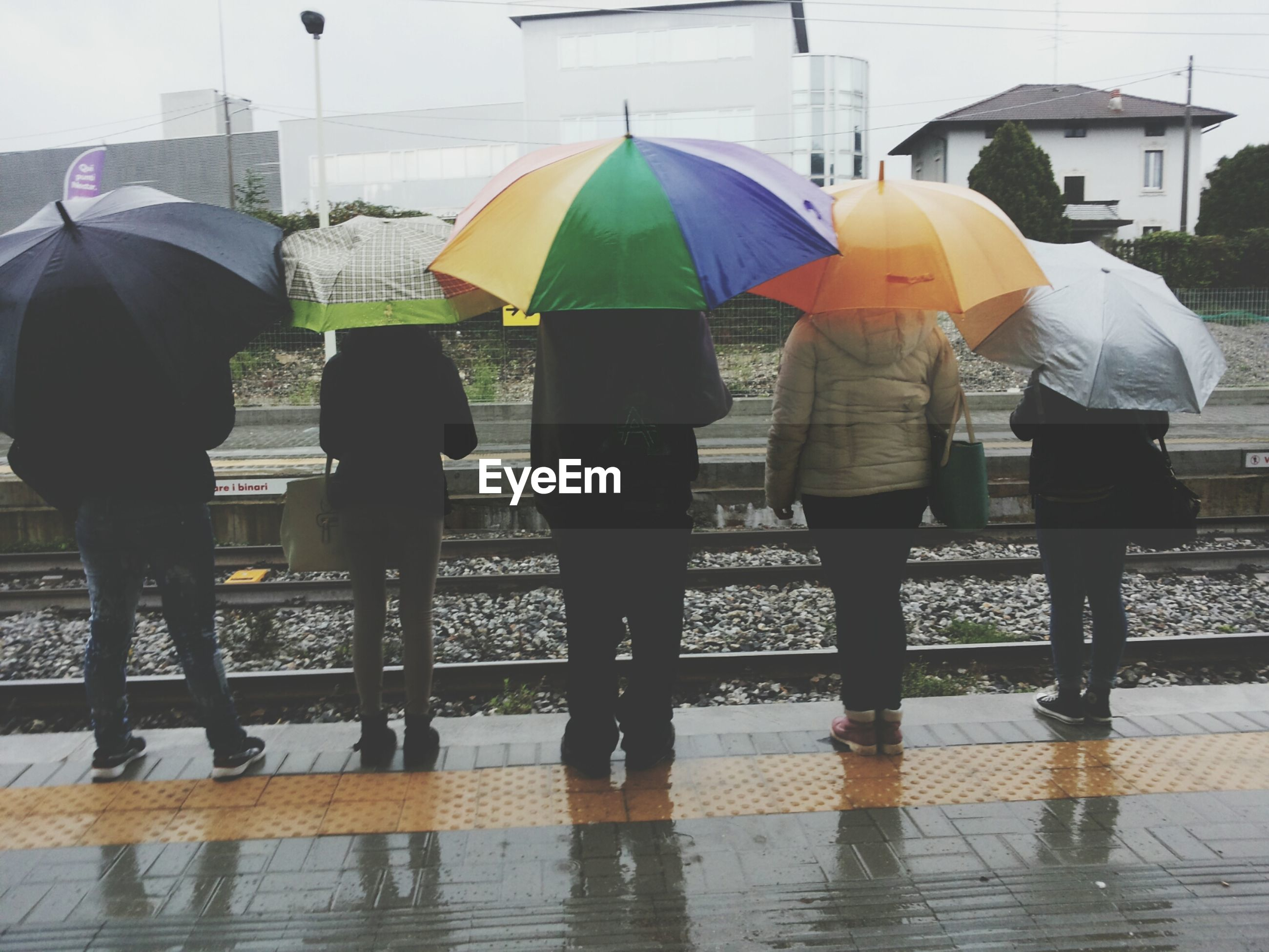 lifestyles, leisure activity, men, standing, person, rear view, walking, umbrella, full length, water, casual clothing, togetherness, childhood, street, medium group of people, reflection, boys