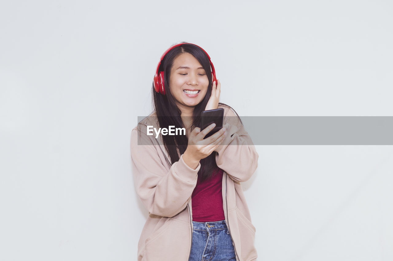 YOUNG WOMAN USING PHONE WHILE STANDING AGAINST WHITE WALL