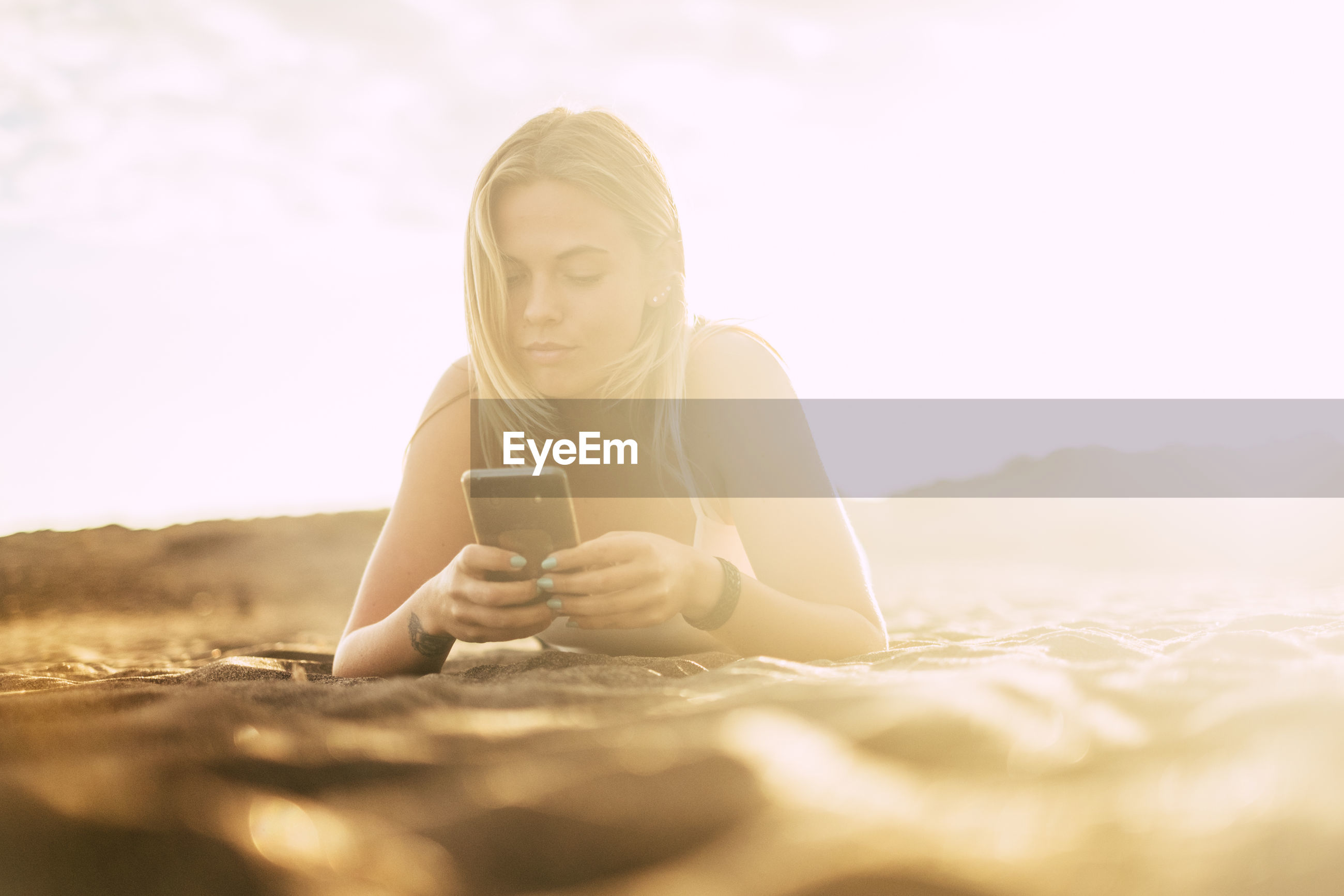 Surface level of young woman using phone while lying on sand at desert